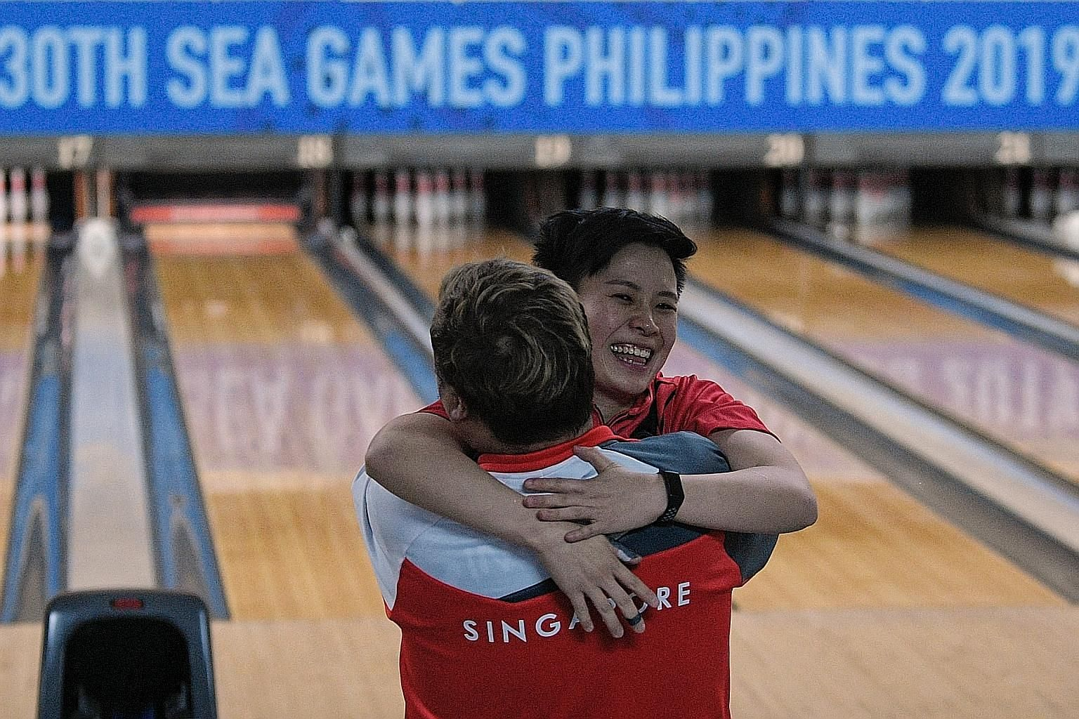 New Hui Fen hugging coach Helmi Chew after defeating Malaysian Siti Safiyah Amirah for the SEA Games women's Masters title in Manila yesterday.