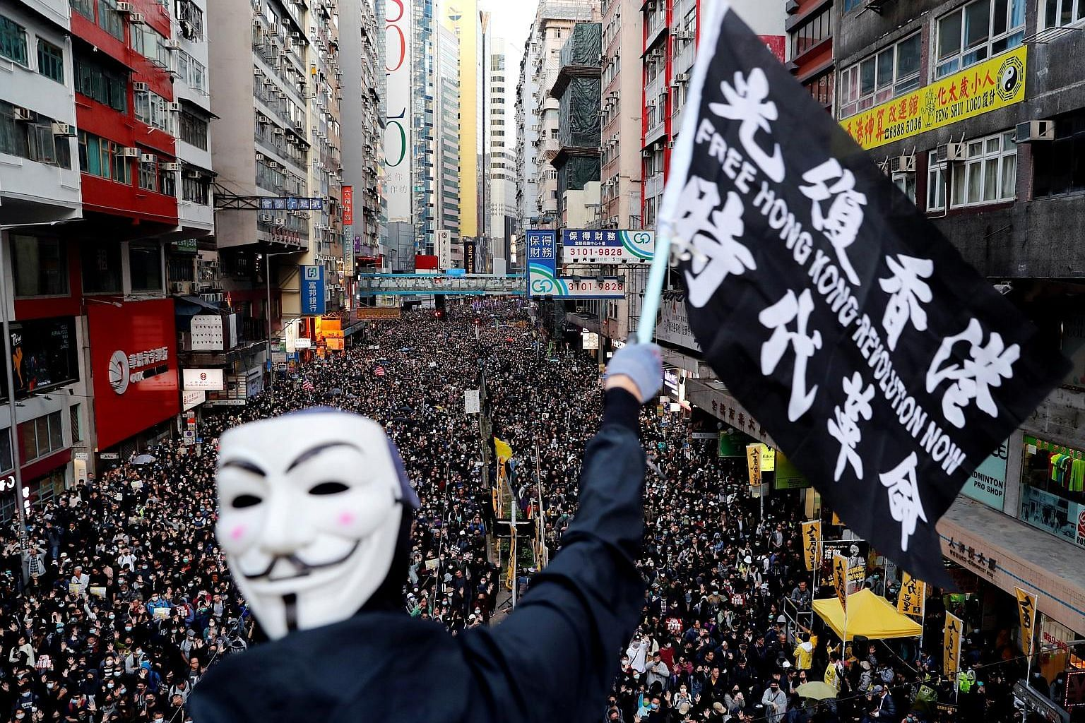 People marching in Hong Kong yesterday. The rally, which began around 3pm, went smoothly but tensions notched up at night when hundreds of protesters in face masks and helmets started building barricades in areas such as Central and Causeway Bay to s