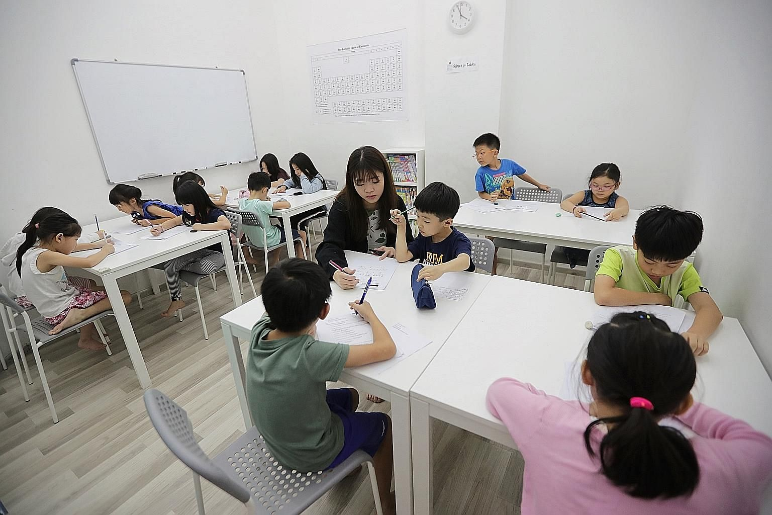 Tutor Calister Ng Jing Ni, 25, with pupils at EduFirst Learning Centre. Families spent about $1.4 billion last year on tuition for their children, according to the Household Expenditure Survey released in July. ST PHOTO: GIN TAY