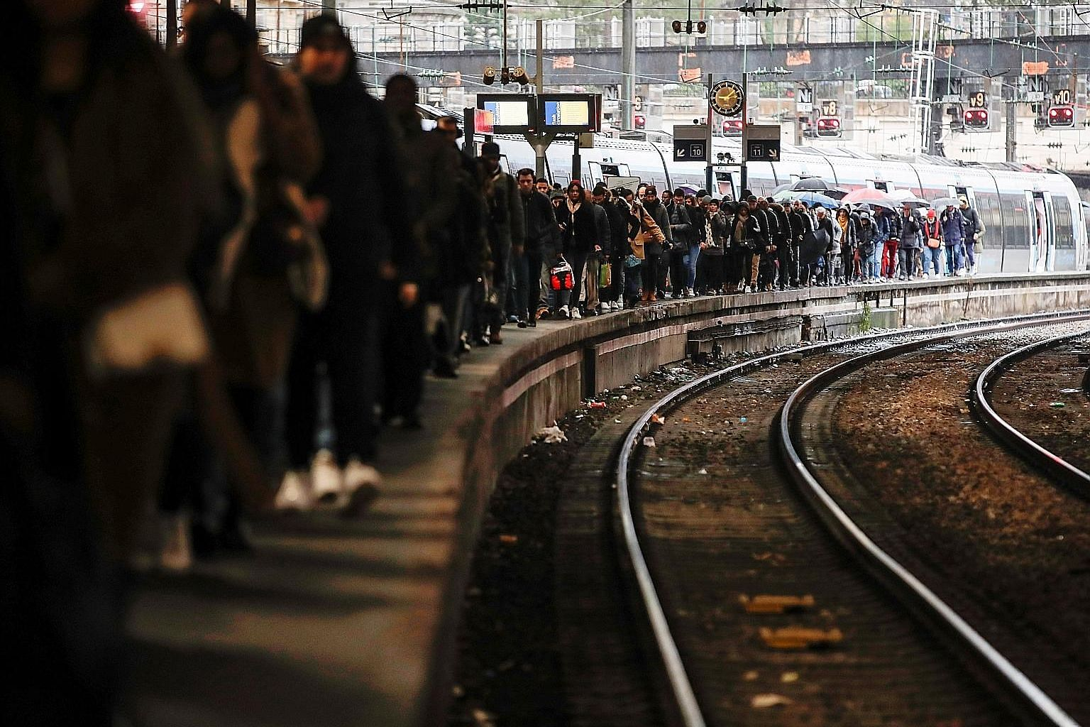 Commuters walking on a platform at Gare Saint-Lazare train station yesterday as a strike continues against the French government's pension reform plans in Paris. Citing safety risks, the SNCF national rail network warned travellers to stay home. PHOT
