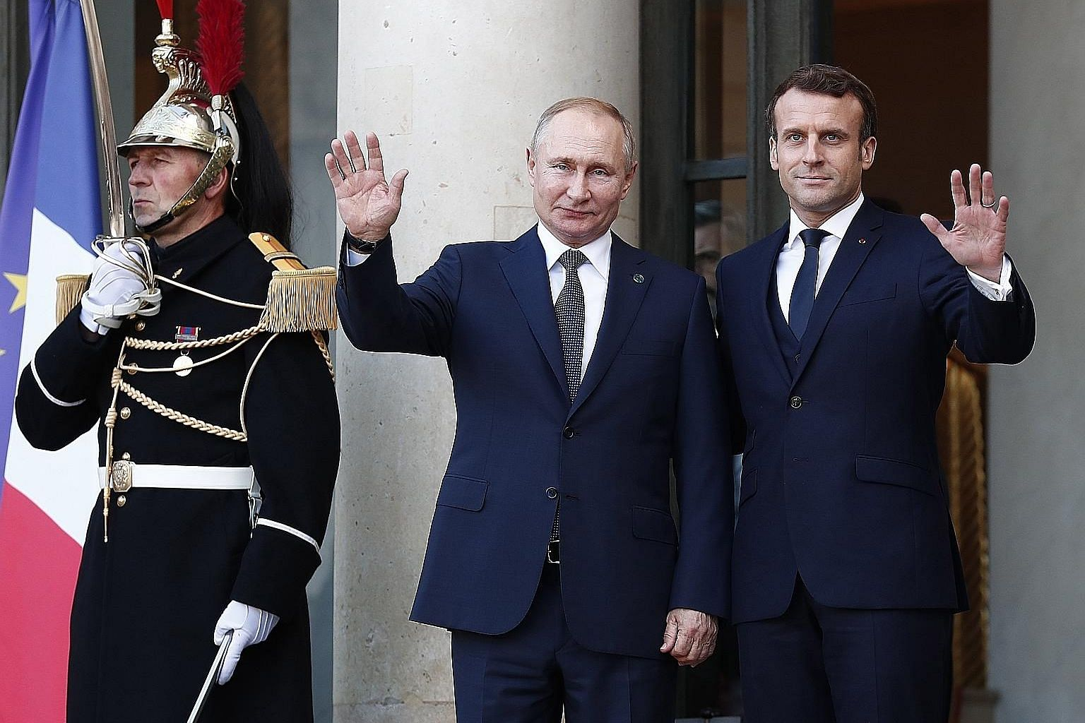 French President Emmanuel Macron greeting Russian President Vladimir Putin as he arrives for the summit on Ukraine at the Elysee Palace in Paris yesterday. Also attending the summit are German and Ukrainian leaders.