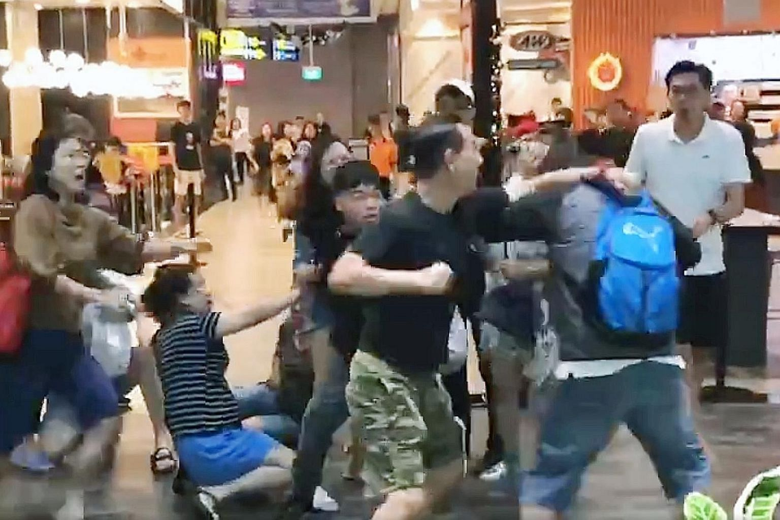 A screengrab of a video showing about 10 people, including women, involved in the brawl in front of fast-food chain A&W at Jewel Changi Airport on Sunday. PHOTO:
