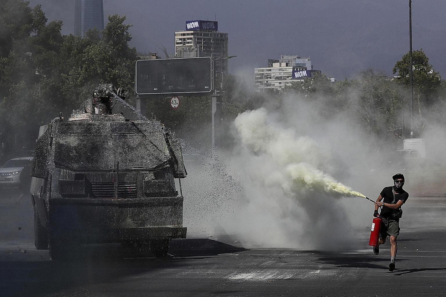 An anti-government demonstrator spraying a fire extinguisher at a police water cannon during a protest in Santiago, Chile, on Monday. Protests calling for equality and better social services have forced President Sebastian Pinera to increase benefits