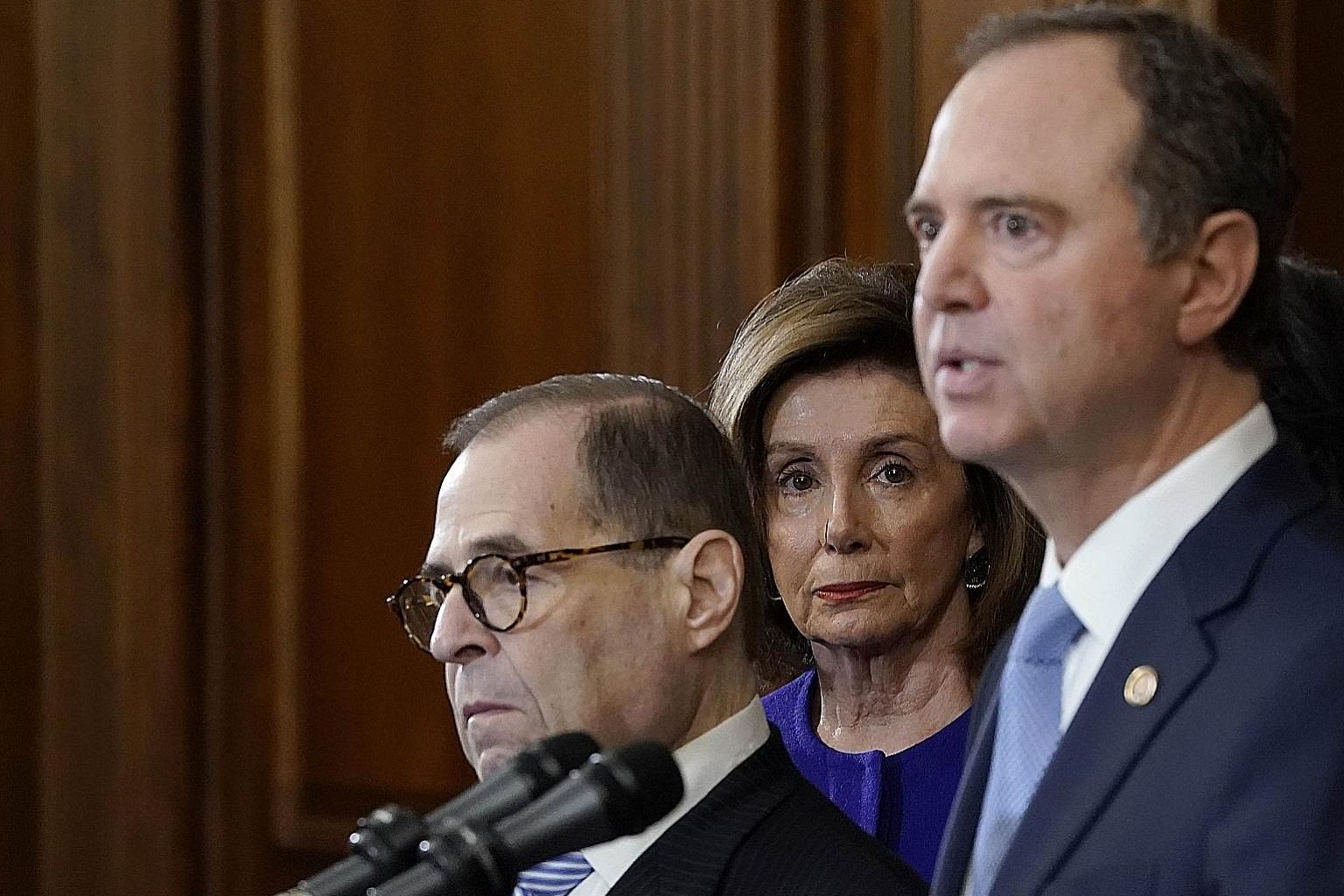 Speaker Nancy Pelosi listening as Mr Adam Schiff (right) and Mr Jerry Nadler announced the next steps in the House impeachment inquiry at the US Capitol in Washington on Tuesday.