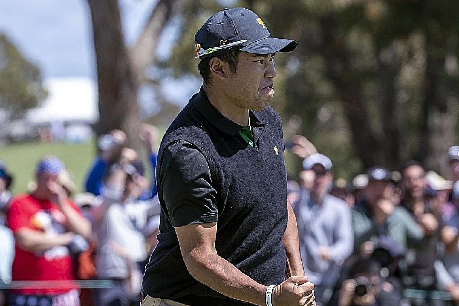 Japanese golfer Hideki Matsuyama pumps his fist after his 25-foot birdie putt on the 17th hole gave him and Taiwanese partner C.T. Pan a 1-up victory over Americans Patrick Reed and Webb Simpson.