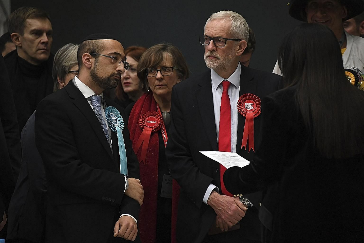 British opposition Labour Party leader Jeremy Corbyn (in red tie) waiting for his seat to be declared in the general election, in Islington, London, yesterday. He comfortably held on to his north London seat but called the party's worst electoral def