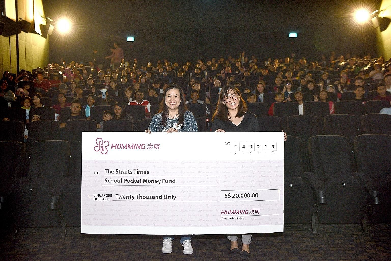 Humming Flowers and Gifts general manager Bernadette Kwan and The Straits Times School Pocket Money Fund operations executive Ho Jia Yan with the $20,000 cheque donated to the fund.