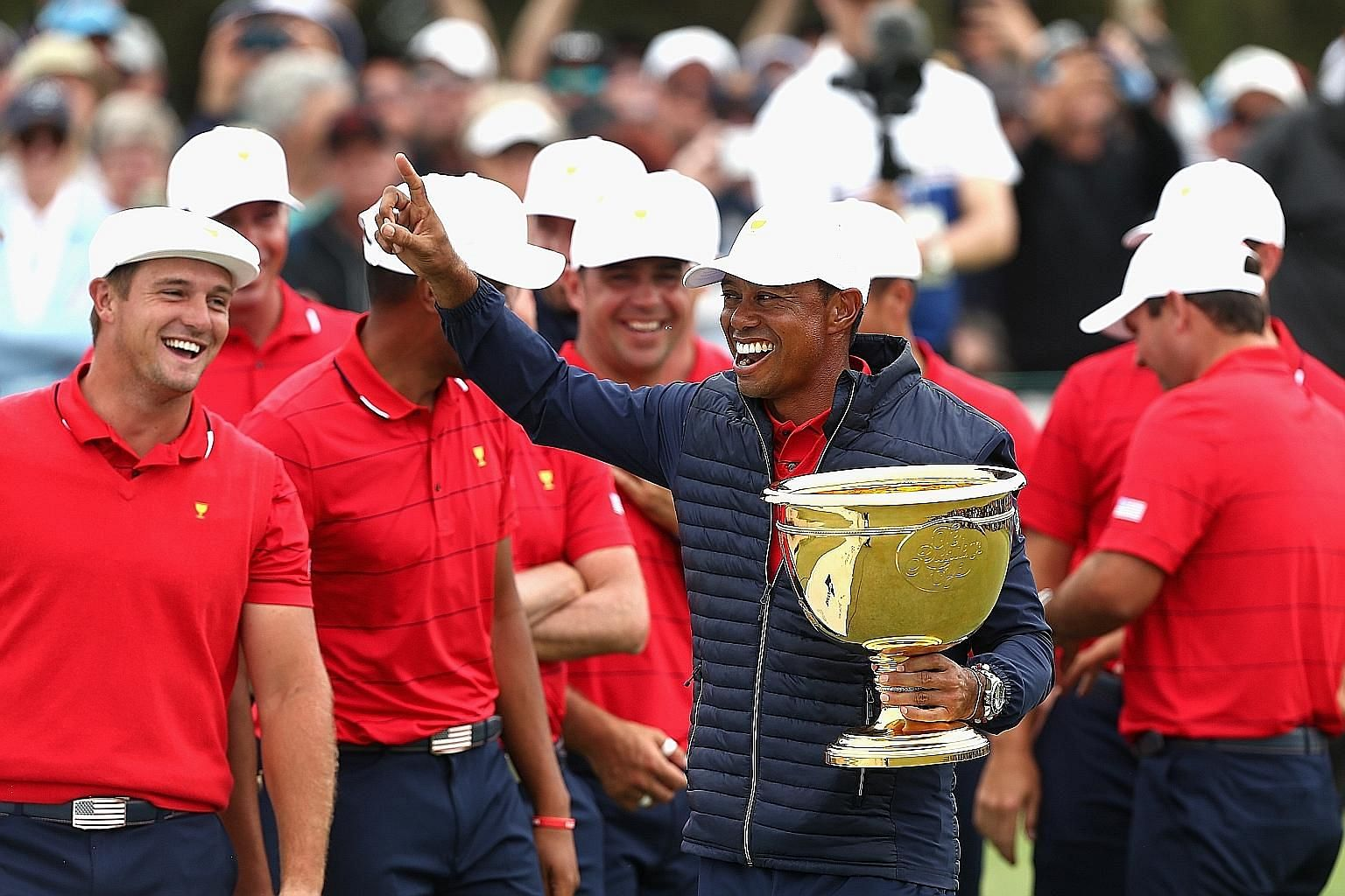 """Tiger Woods celebrating the US team's Presidents Cup victory with his teammates yesterday. The playing captain said he """"trusted all my 11 guys implicitly from the very get go""""."""