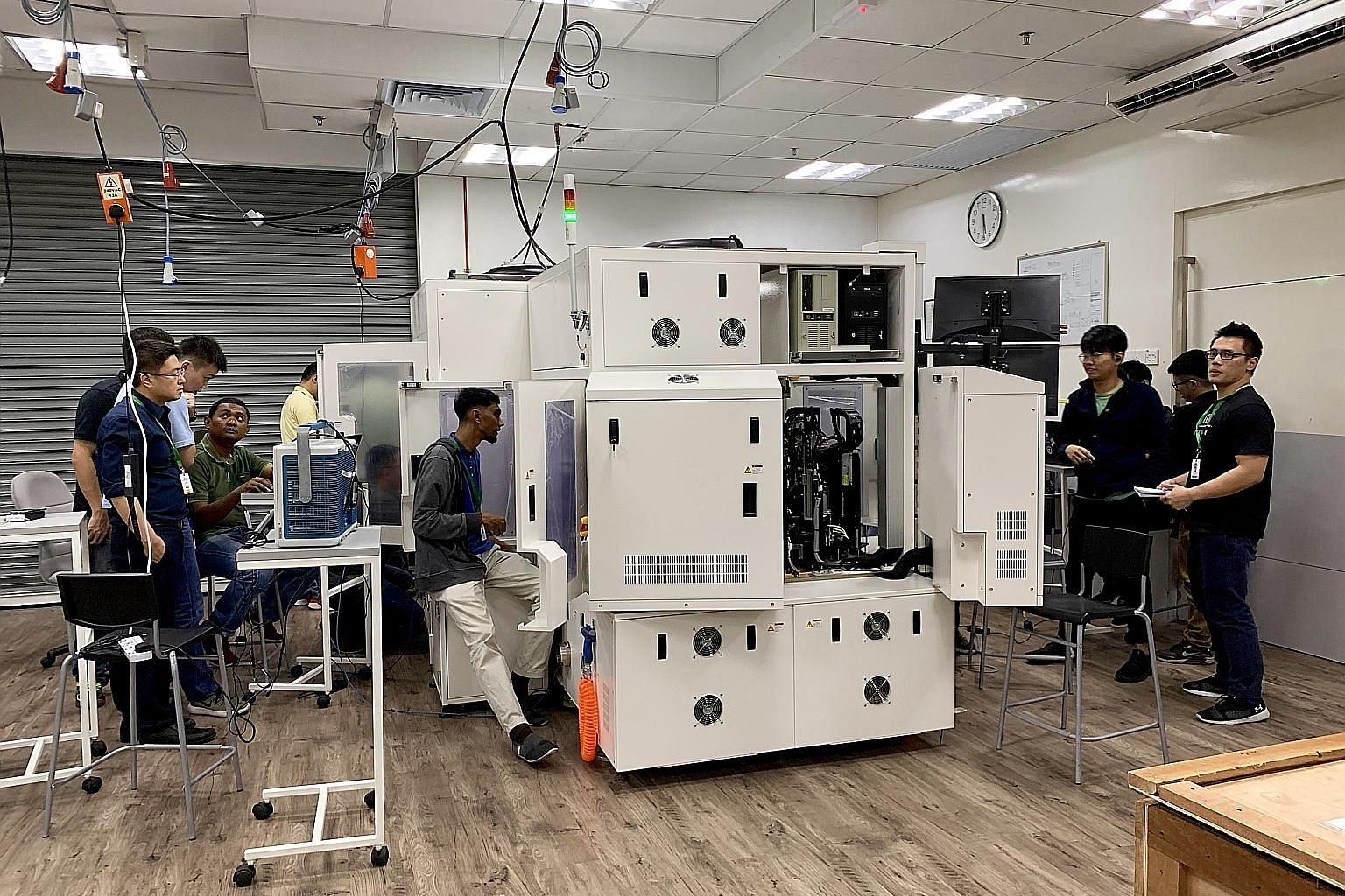 """Above: Datuk Seri Wong Siew Hai, chairman of the American Malaysian Chamber of Commerce's electronics committee, says Penang needs to win the """"talent war"""" to ensure investors stay. Left: Staff at high-technology equipment maker Pentamaster, which has"""