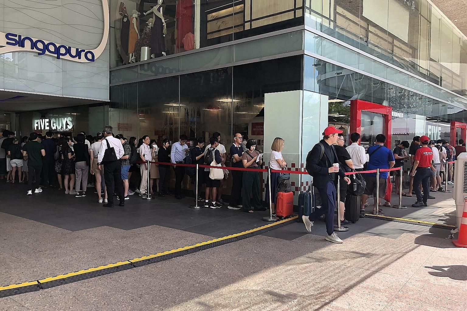 Five Guys Singapore (left) had about 100 people in line prior to the store's opening at 11am. The brand prides itself on its hand-cut fries cooked in peanut oil, as well as burger patties with an 80-20 lean meat-to-fat ratio.