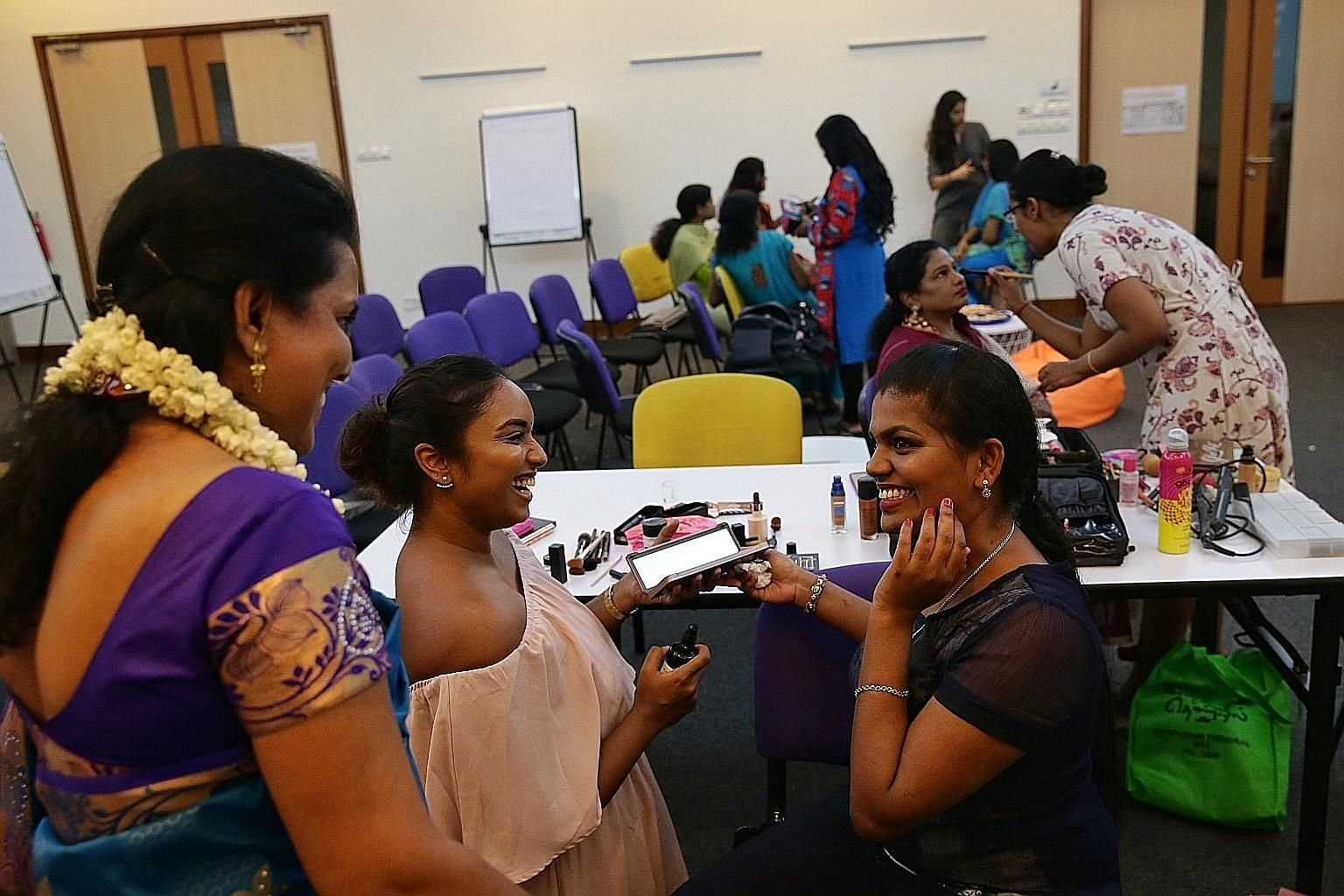 Indian migrant worker Anukrishna (at right) all smiles after having her make-up done by volunteer Aavishka Ragam during a Mother's Day event organised by Women of Shakti at the National Volunteer and Philanthropy Centre's A Good Space in May.