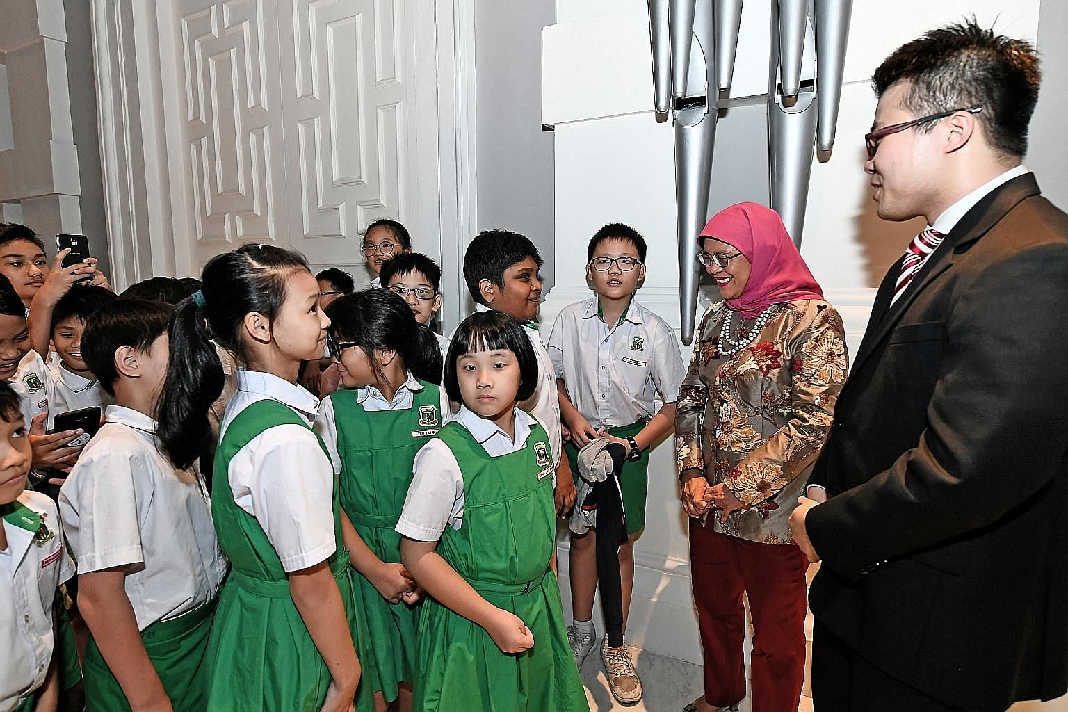 President Halimah Yacob and guitar soloist Kevin Loh meeting Bukit Panjang Primary School pupils at the President's Young Performers concert, held at Victoria Concert Hall in September.