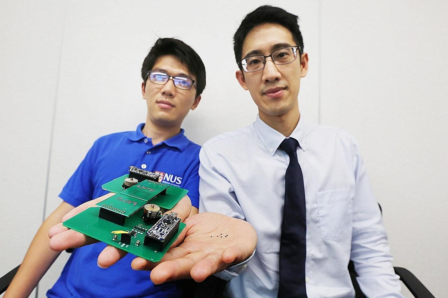 Left: National University of Singapore Assistant Professor John Ho (in white shirt) and PhD student Dong Zhenya with a prototype of the wireless reader their team created to easily read signals from microsensors less than 1mm long. They also develope