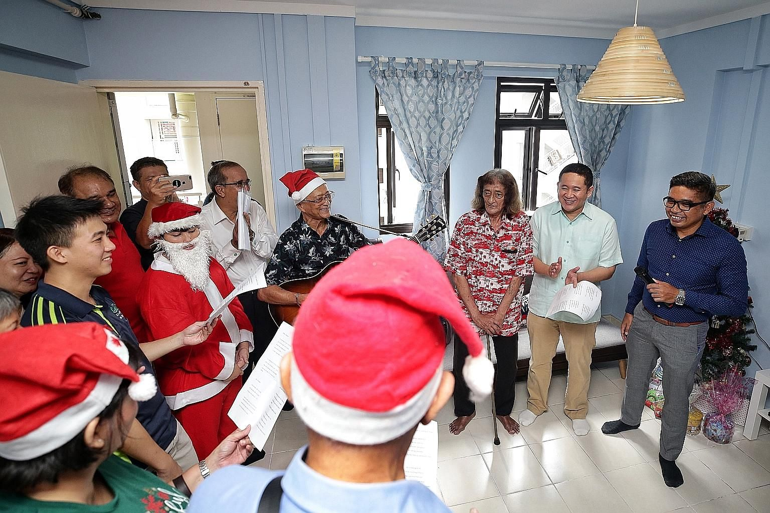 Mr Victor Louis De Foe in his spruced-up home in Woodlands. Volunteers from Jamiyah Halfway House painted the flat and installed new appliances. They also got him a Christmas tree and had it decorated. Mr De Foe (third from right) with volunteers fro