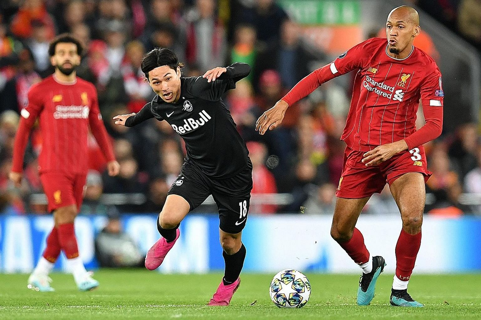 Salzburg's Takumi Minamino vying for the ball with Liverpool's Fabinho during their Champions League clash at Anfield in October. The Japanese, who can play as a winger or an attacking midfielder, impressed Reds boss Jurgen Klopp during his team's 4-