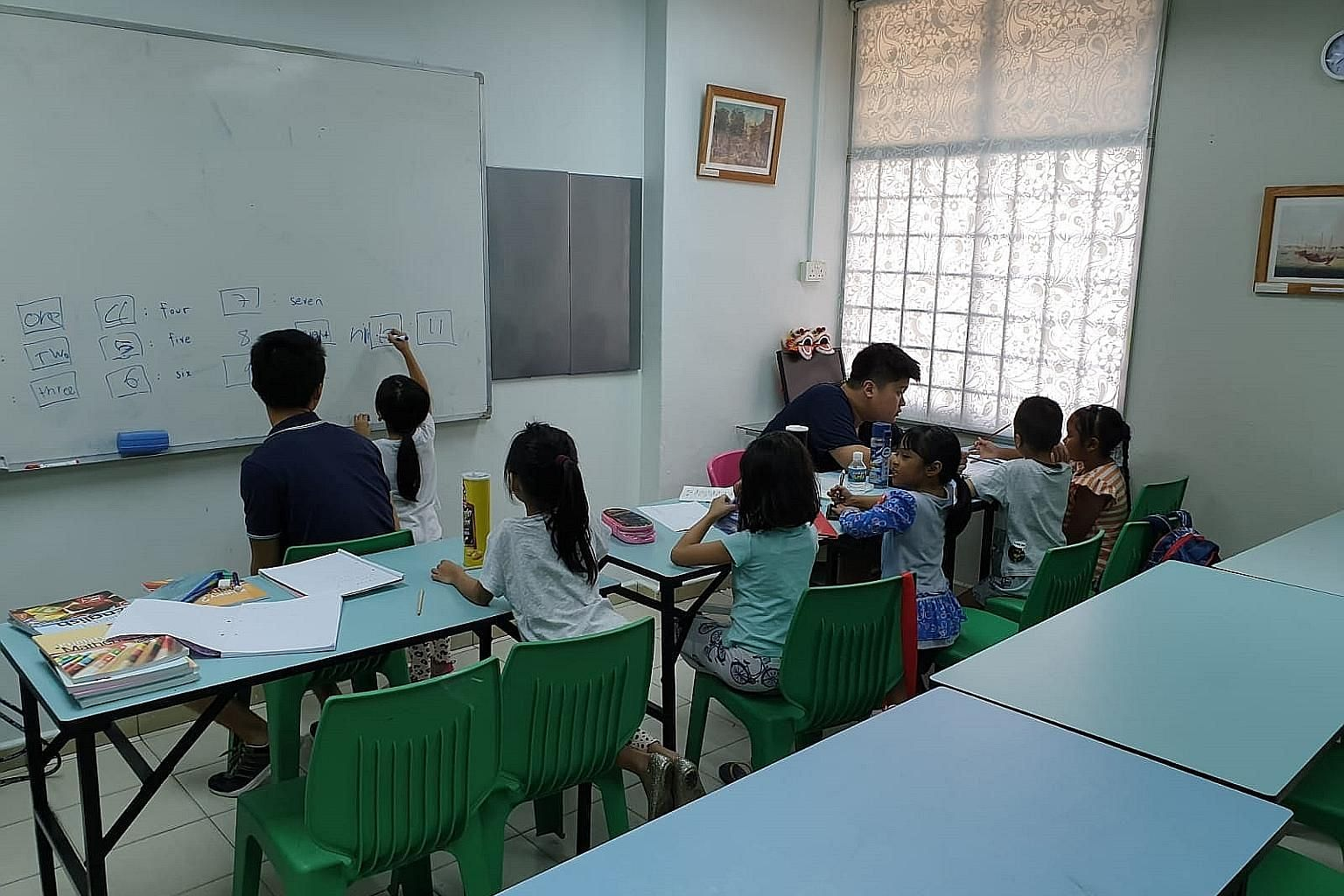 A Budding Minds tuition session in progress at the We Love Learning Centre in Henderson. Mr Chua Tze Hean, who started the project, says the volunteer tutors try to make content more interesting by showing the children real-life applications of their