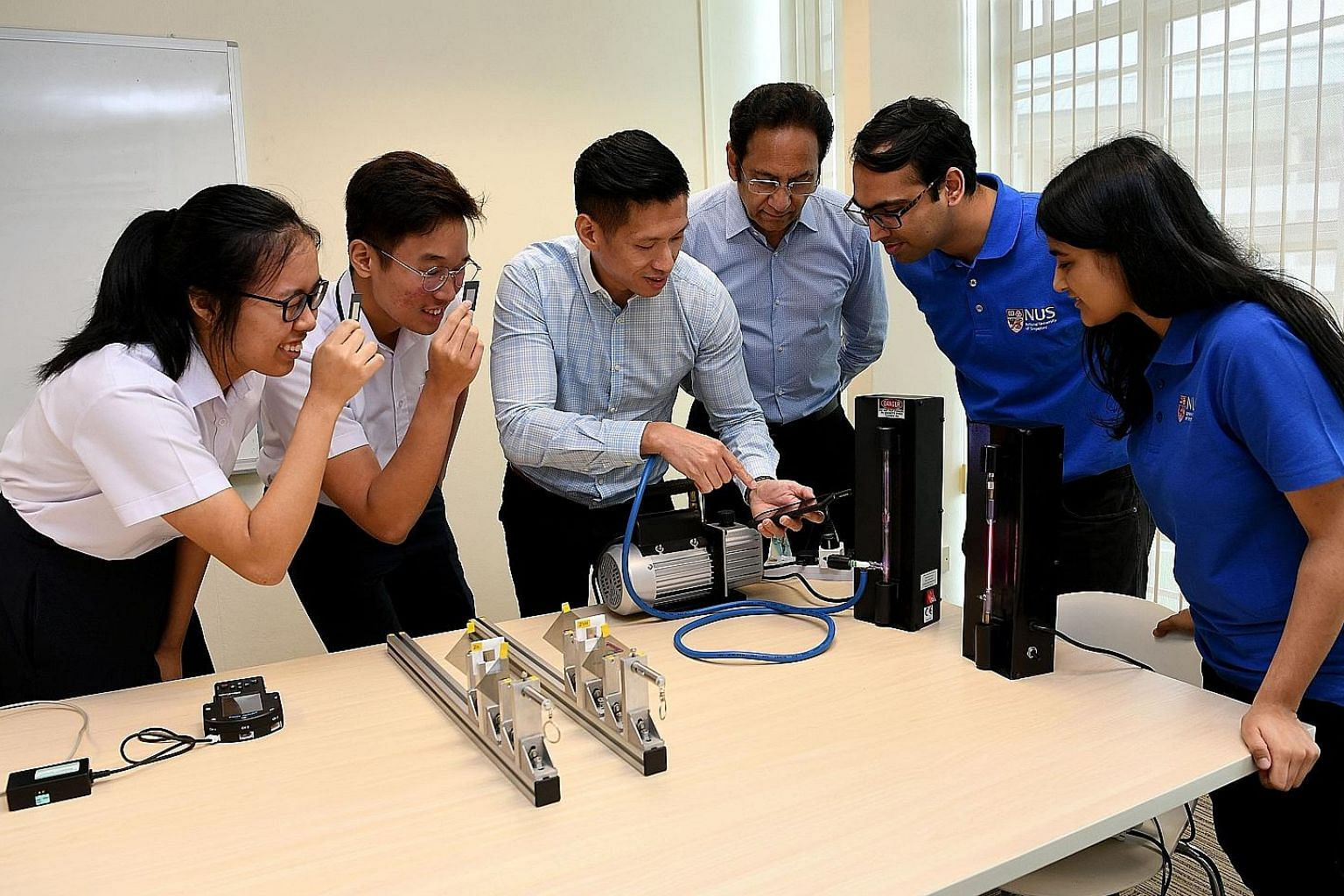 Jurong Pioneer Junior College's head of department for curricular development and innovation Edwin Lim using a mobile phone spectrometer, which measures light wavelengths. With him (from far left) are students Narahda Lim and Haw Jin Yu; Professor Th