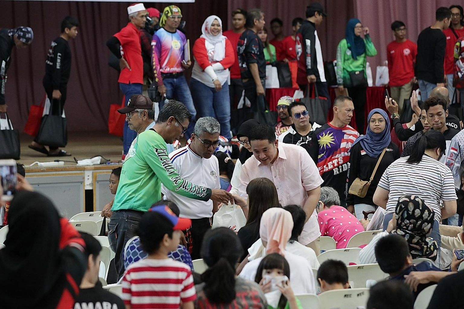 Senior Parliamentary Secretary for Home Affairs and Health Amrin Amin (centre) helping to give out food bags at Woodlands Community Club yesterday. Volunteers at the event included members of 23 motorcycle groups.