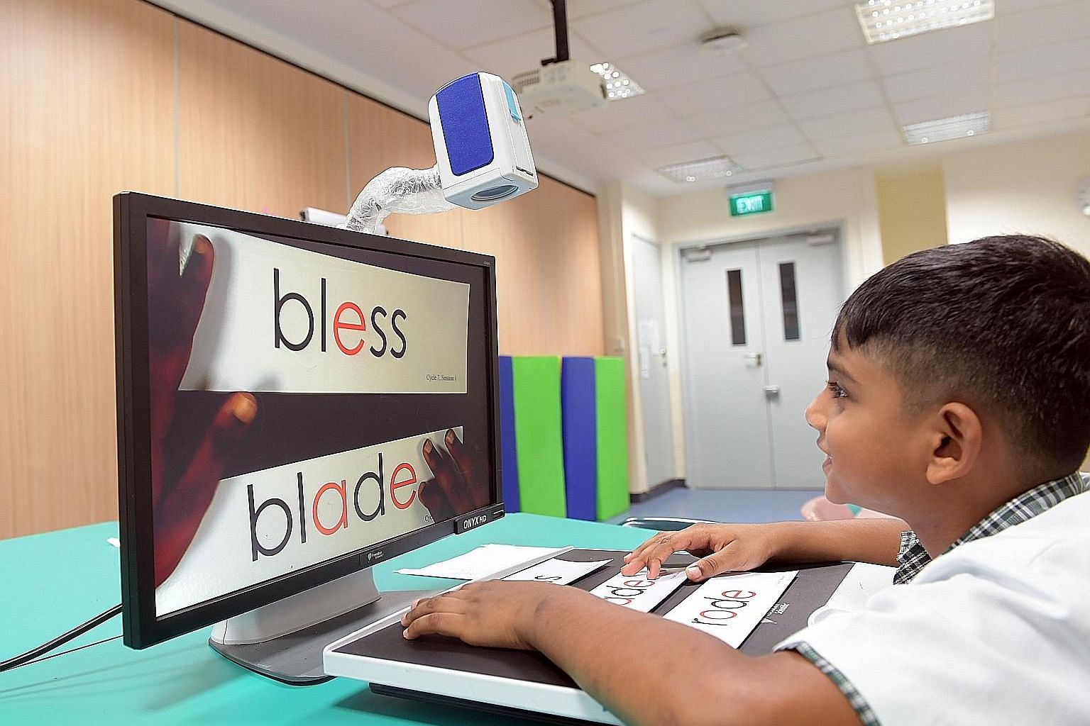 Tejas Mahendran, seven, who has low vision due to cone-rod dystrophy, uses a portable video magnification system that enlarges words on the class whiteboard and materials like worksheets to help him read.