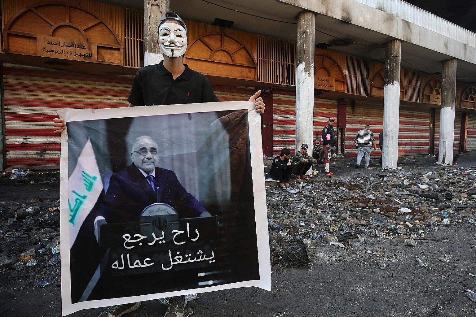 """A protester in Baghdad on Dec 5 with a poster of newly resigned prime minister Adel Abdel Mahdi. The Arabic words mean """"He will now join the labour"""". PHOTO: AGENCE FRANCE-PRESSE"""