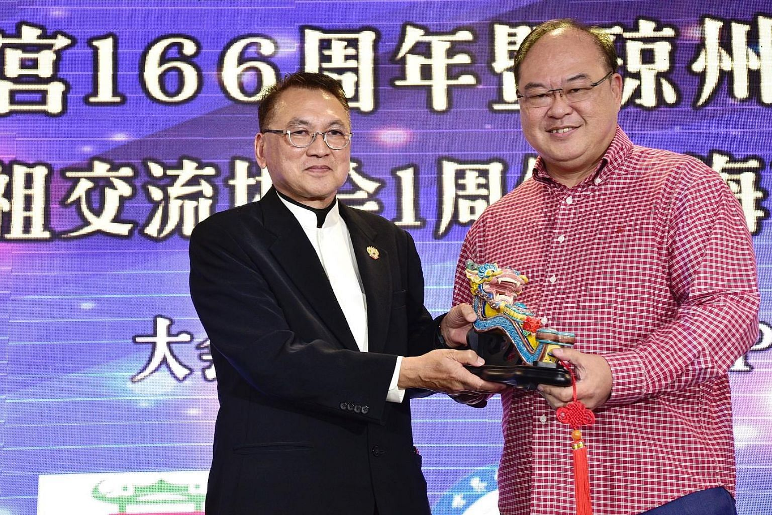 Kheng Chiu Tin Hou Kong and Burial Ground chairman Foo Jong Peng (left) presenting a memento to Mr Tan Aik Hock, president of the Singapore Federation of Chinese Clan Associations, during the launch of the Hainan Federation yesterday.