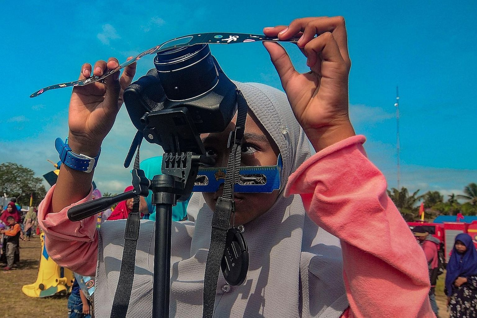 A girl placing a filter in front of her camera to take photos of the annular solar eclipse in Siak, in Indonesia's Riau province, yesterday.