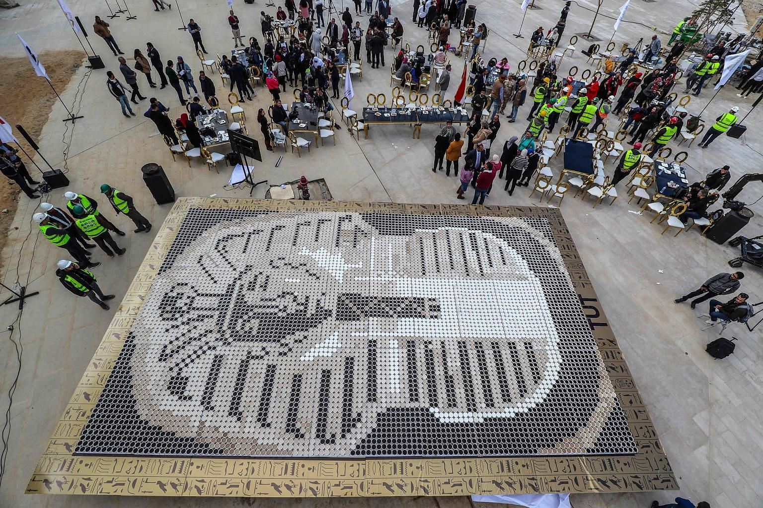 People gathering around a mosaic of Egyptian Pharaoh Tutankhamun's death mask made of 7,260 cups of coffee on Saturday. The mosaic, in front of the newly-built Grand Egyptian Museum in Giza, beat the 2012 world record set by a similar mosaic in the U