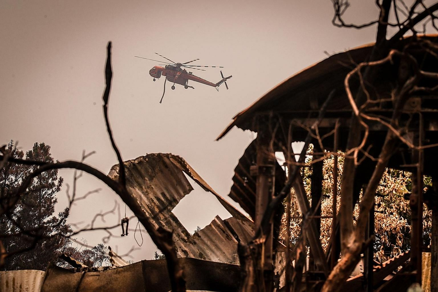 A helicopter with a water hose flying over a house destroyed by bush fires near the town of Bilpin, New South Wales, on Sunday. The state has borne the brunt of the fires, which have burned out more than 2.5 million ha of forest and bush land and des