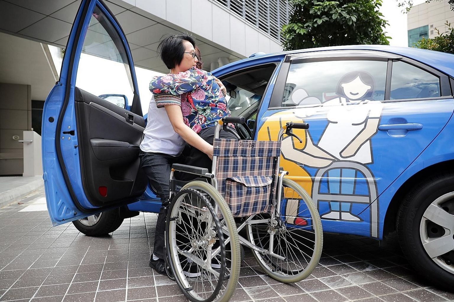 TTSH senior therapy assistants Poh Kuat Hong (left) and Cindy Quek demonstrating the car transfer training with a decommissioned ComfortDelGro taxi. For caregivers, it involves learning the proper technique of positioning and then lifting or helping