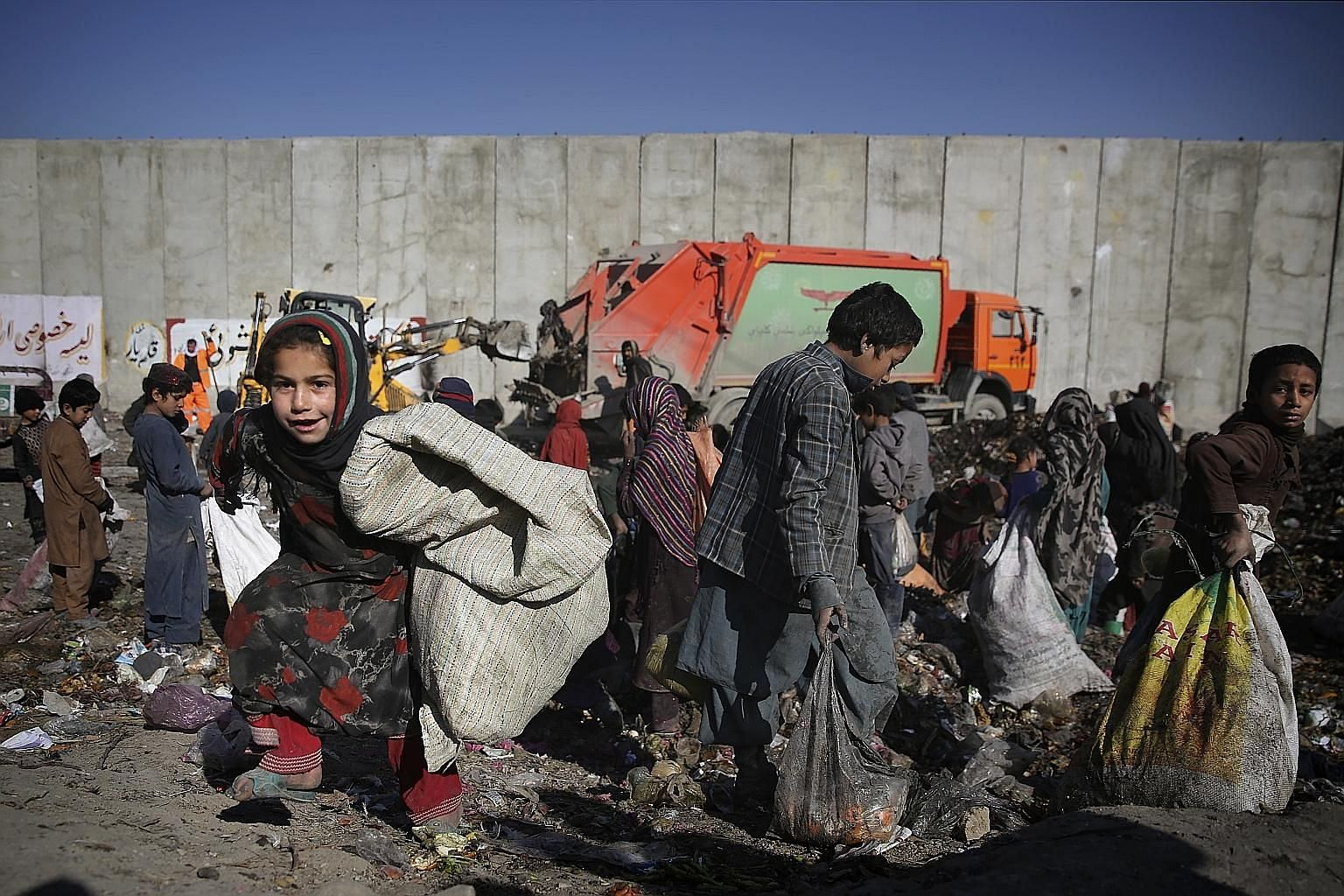 """Internally displaced Afghan children searching a dump site in Kabul. The writer says that as recently as 1981, 42 per cent of the planet's population endured """"extreme poverty"""", defined by the United Nations as living on less than about US$2 ($2.70) a"""
