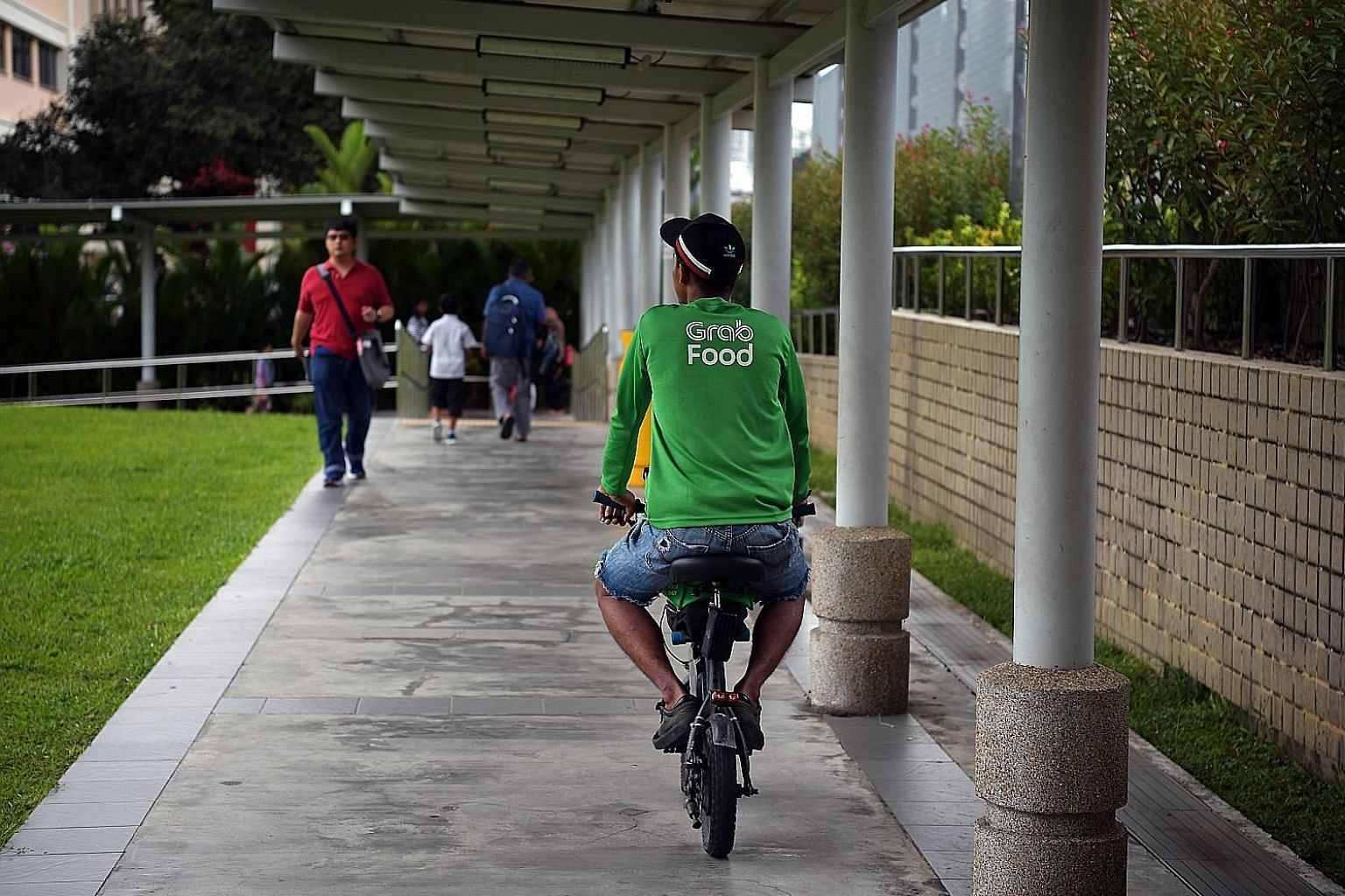 A Grab deliveryman riding a personal mobility device on a pavement next to Bishan MRT station last May, before a ban was introduced last November. GrabFood said yesterday that riders caught riding e-scooters on footpaths will no longer work for the c