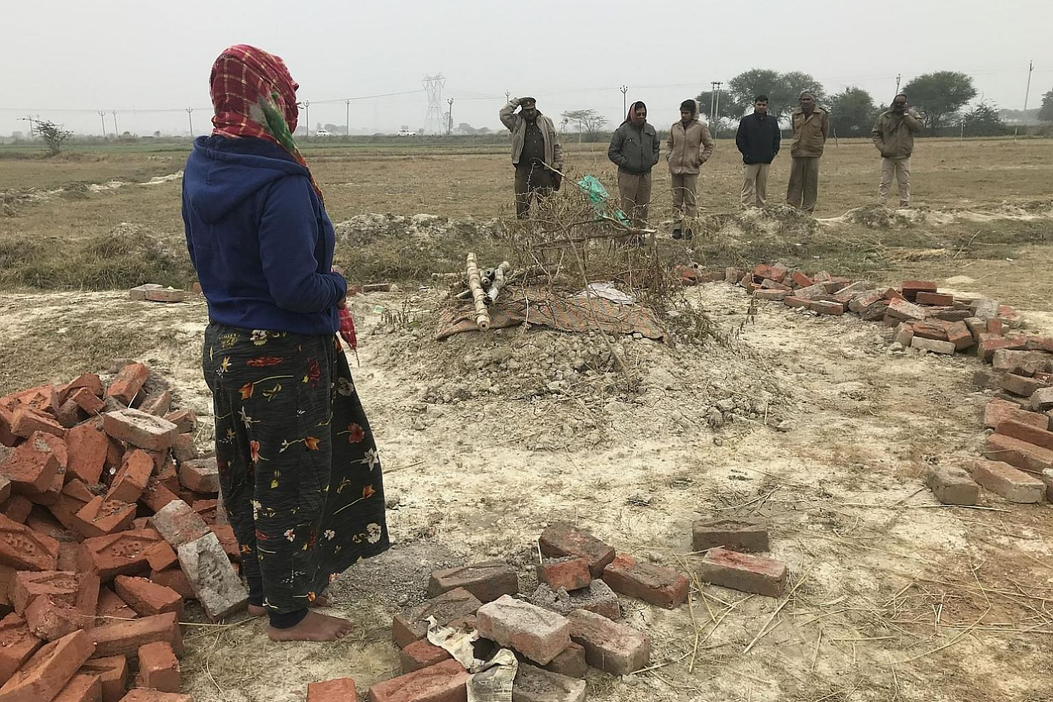 A woman at the grave of her sister who was raped and later set on fire, allegedly by two of her accused rapists, in a village in Unnao. Accompanying her on the visit to the grave were police officials assigned to protect the family. She said her sist