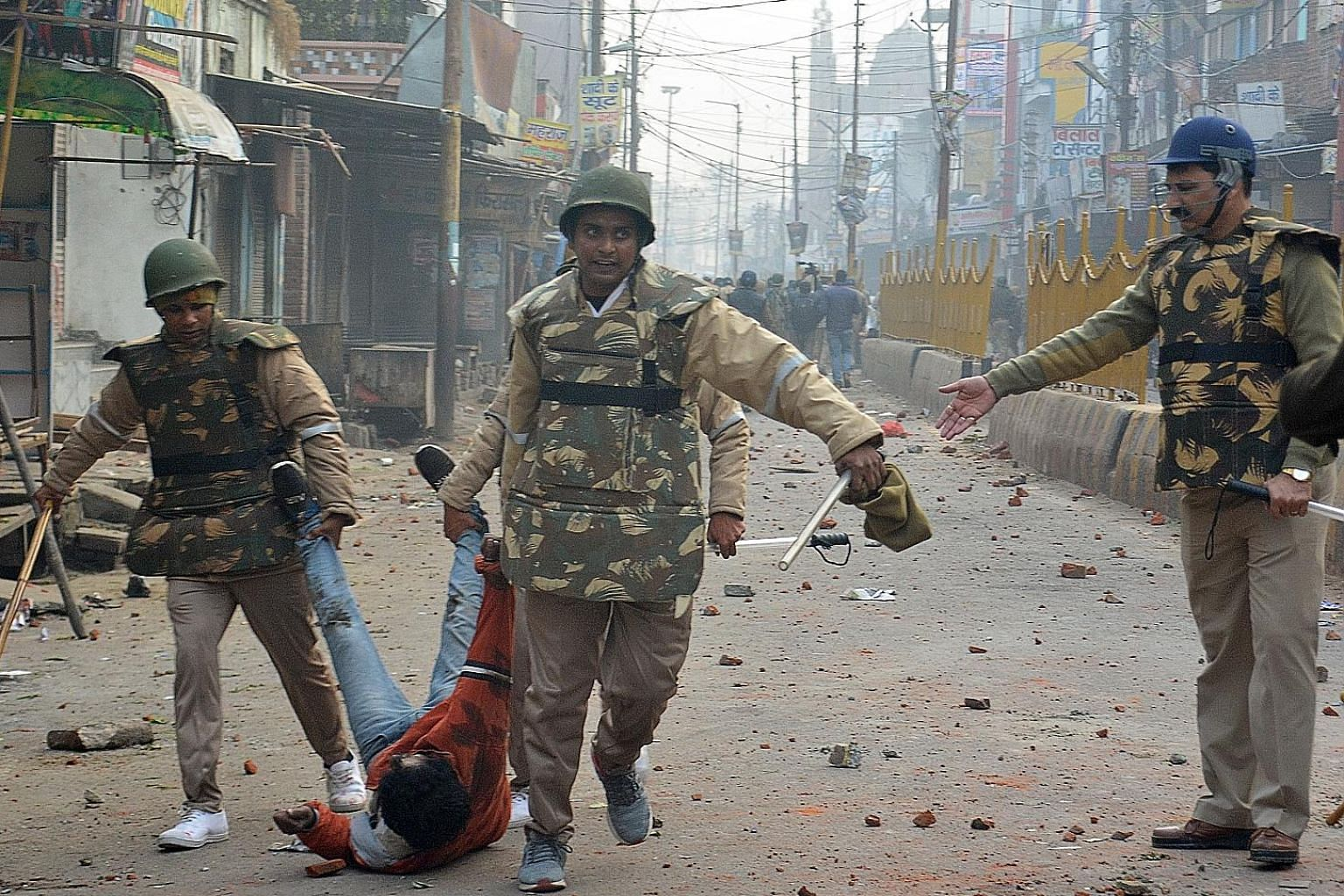 Security personnel detaining a protester during demonstrations in Meerut against India's Citizenship Amendment Act on Dec 20. Five men were shot dead in what locals call police excesses.
