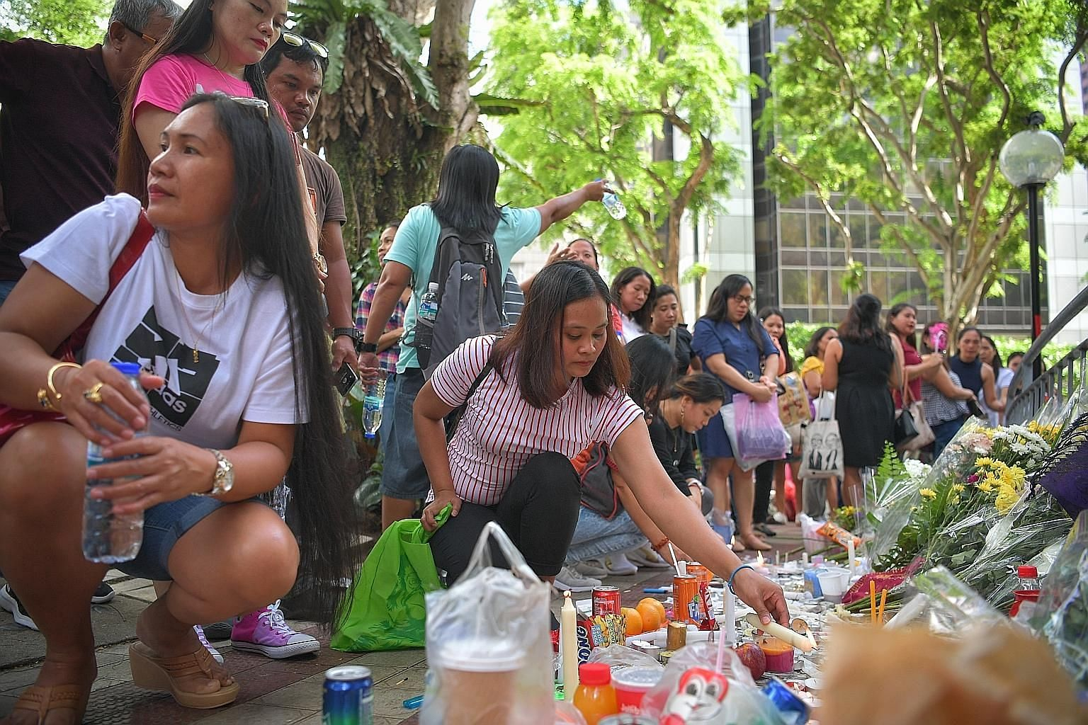 Mourners at a makeshift memorial near the site of the Dec 29 accident at Lucky Plaza on Sunday. ST PHOTO: ARIFFIN JAMAR