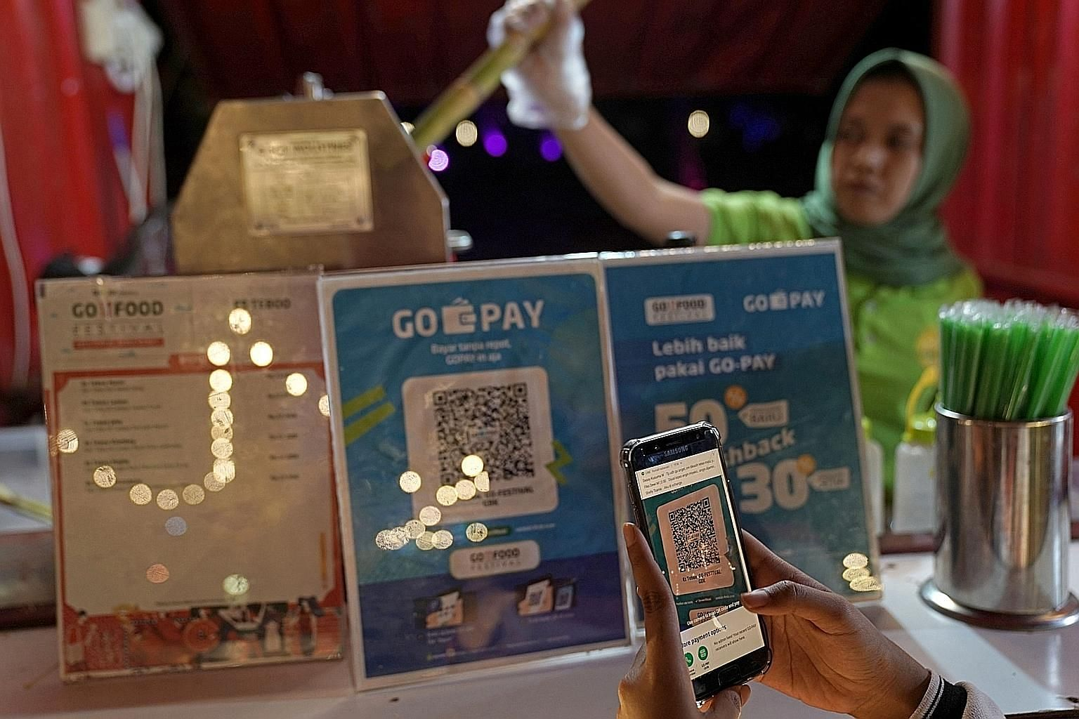 A customer using digital payment at a stall at the Go-Food Festival in Jakarta last year. Financial technology is booming in Indonesia, beginning with digital payments, says the writer, adding that there is a natural synergy of digital payments with