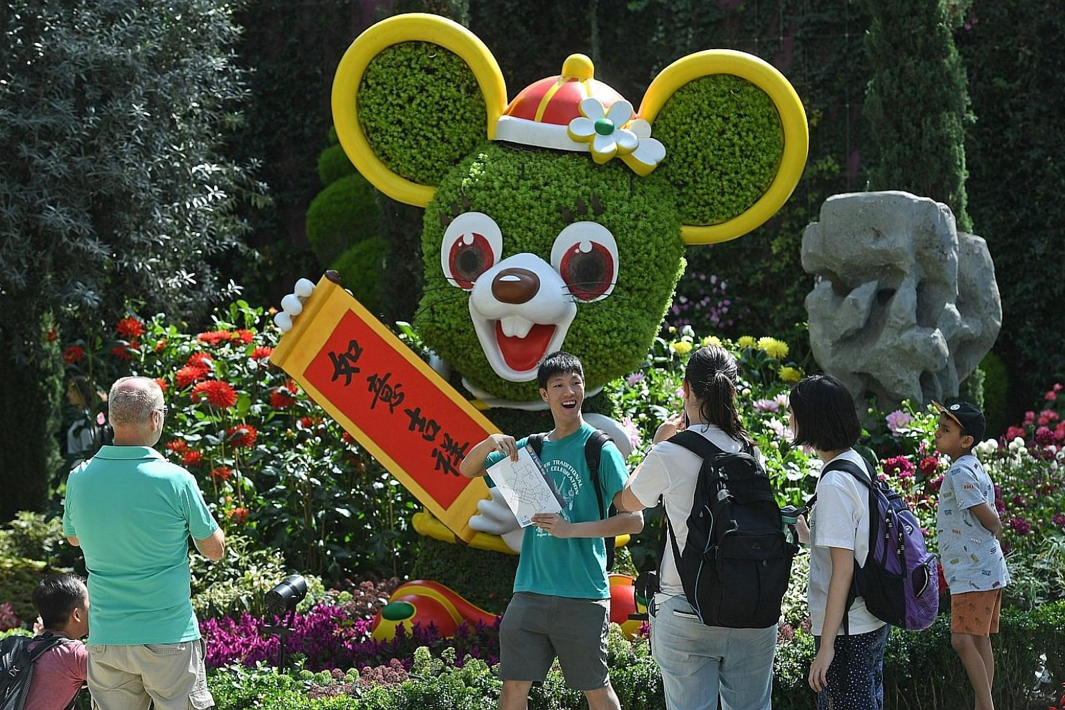 """A 5m-tall medallion of the Chinese word fu, which means blessing, showcases deep red kalanchoe blossoms against a striking background of yellow pansies. A pair of """"golden"""" rats made up of sedum and begonia plants now appear green as the flowers have"""