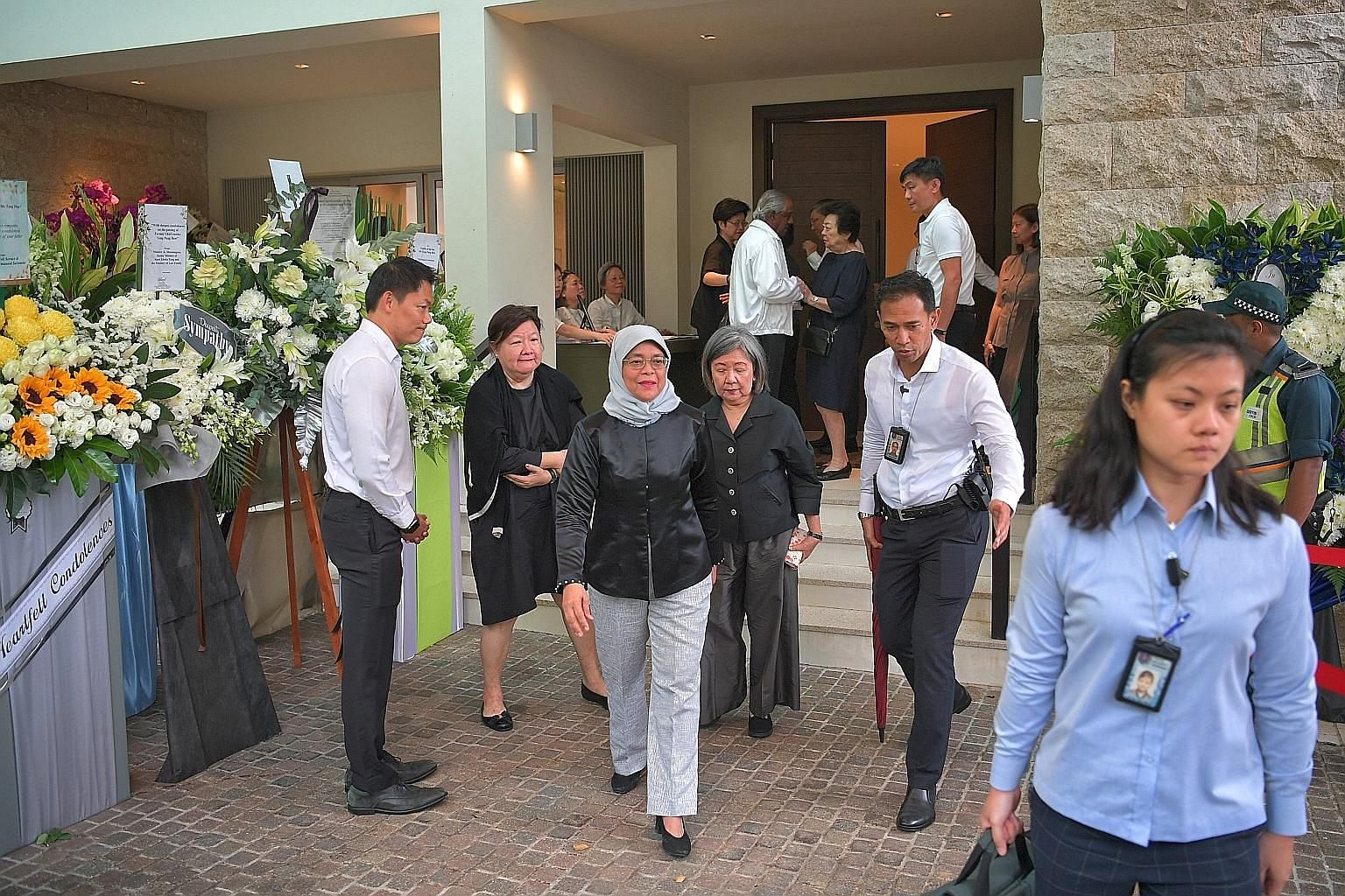 """Chief Justice Sundaresh Menon arriving at the wake with his wife. He described Mr Yong as having """"a wonderful heart for the people who worked with him"""". Ms Phyllis See (centre, in white), speaking to reporters at the wake yesterday. Ms See, 71, was s"""