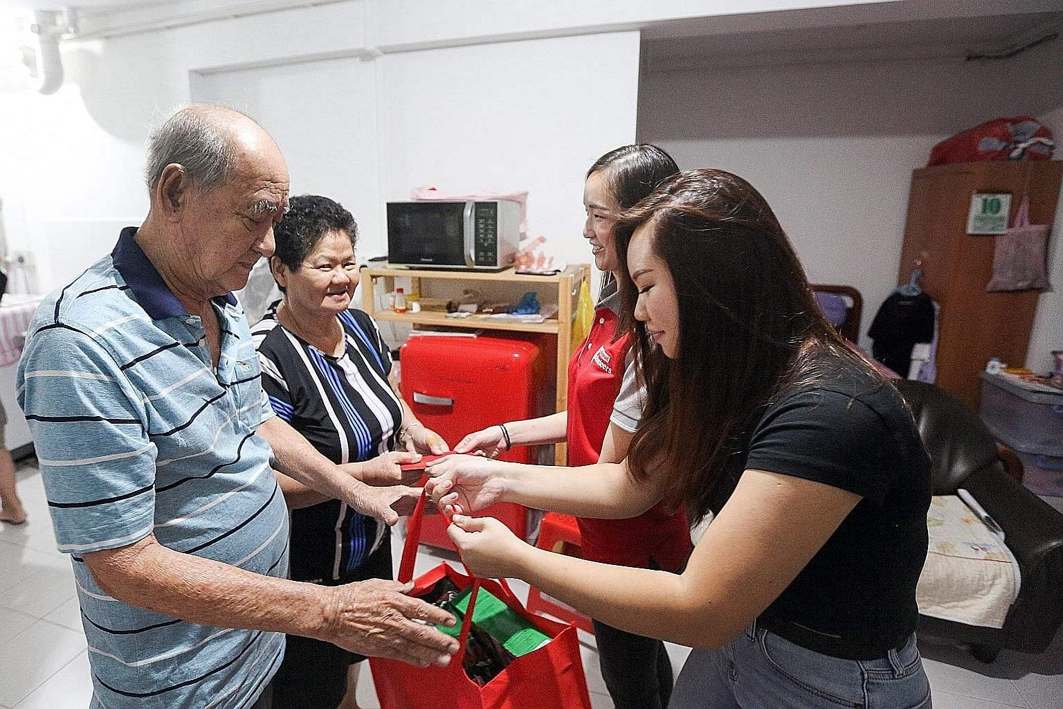 Retiree Tan Lay Swee (left), 79, and housewife Lew Siew Yin, 74, receiving a festive pack and hongbao from volunteers Florence Sing (in black), 20, and Jerrine Or, 26. Volunteers from Keppel Group and Republic Polytechnic distributed the bags which w
