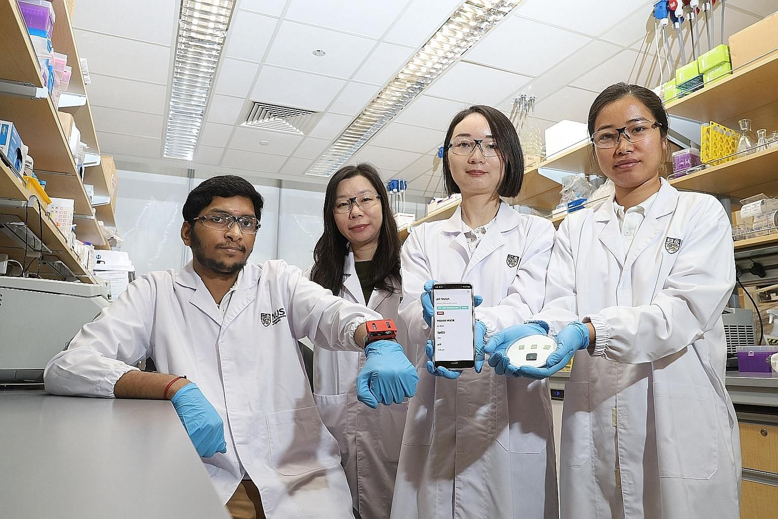 (From left) Doctoral student Ananta Narayanan Balaji, wearing the pH Watch, with Assistant Professor Shao Huilin, Dr Wang Bo and doctoral student Chen Yuan, who is holding the pulse oximeter and pH sensor. The team of researchers from the National Un