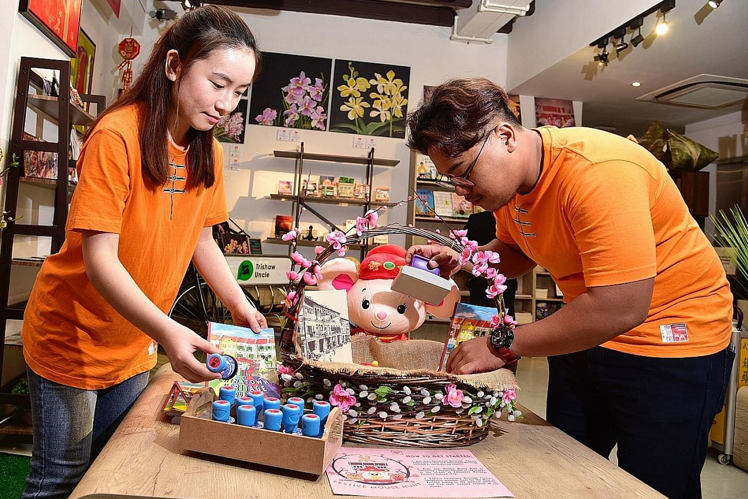 Chinatown Heritage Centre staff Tan Ching Ying, 22, and Muhammad Luthfil Hady, 21, with the ink stamps and journals which visitors can buy to collect the stamps.