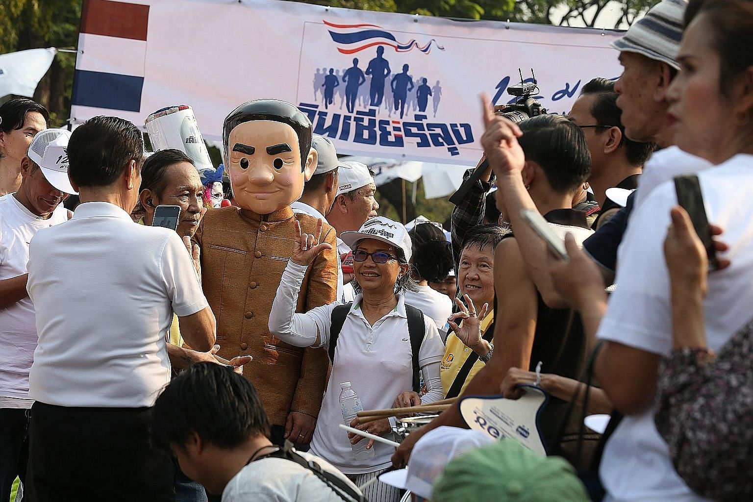 """A supporter of Mr Prayut Chan-o-cha, dressed as the Thai Prime Minister (top), taking part in a """"Walk for Prayut"""" event at Lumpini Park in the Thai capital Bangkok yesterday. The rally was held to counter an anti-government event (above) dubbed """"Run"""