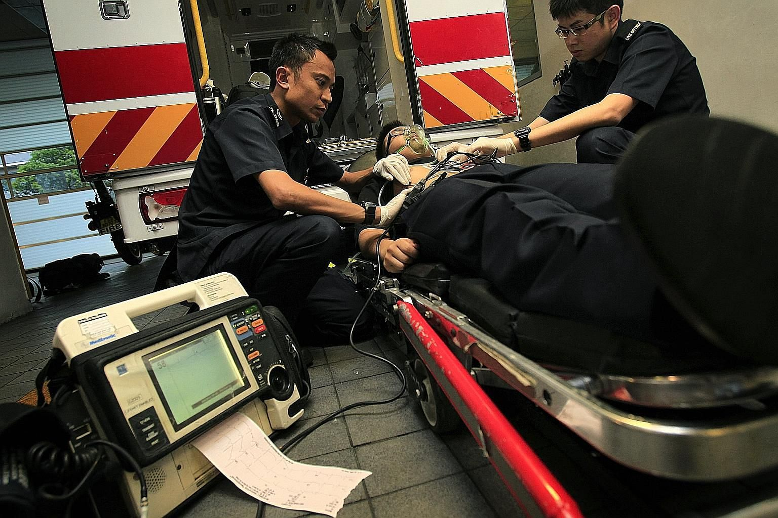 A 2011 file photo of a paramedic and a trainee demonstrating how an electrocardiogram is performed on a patient. NUH is one of just two places here which can deal with even the most complex heart problems at any time, day or night. The other is Natio