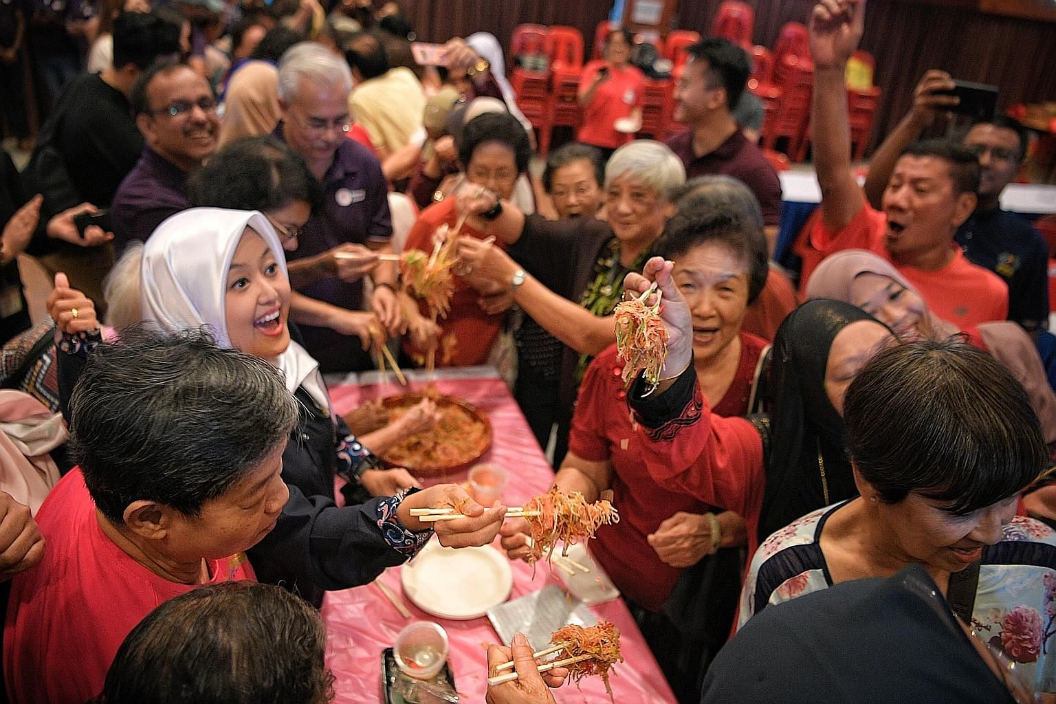 Ms Rahayu Mahzam, MP for Jurong GRC and an adviser to the PA Mesra youth sub-committee, joining in the lo hei session with seniors from Thye Hua Kwan Social Service Hub in Bukit Batok East and the Concern and Care Society during the event at Bukit Ba
