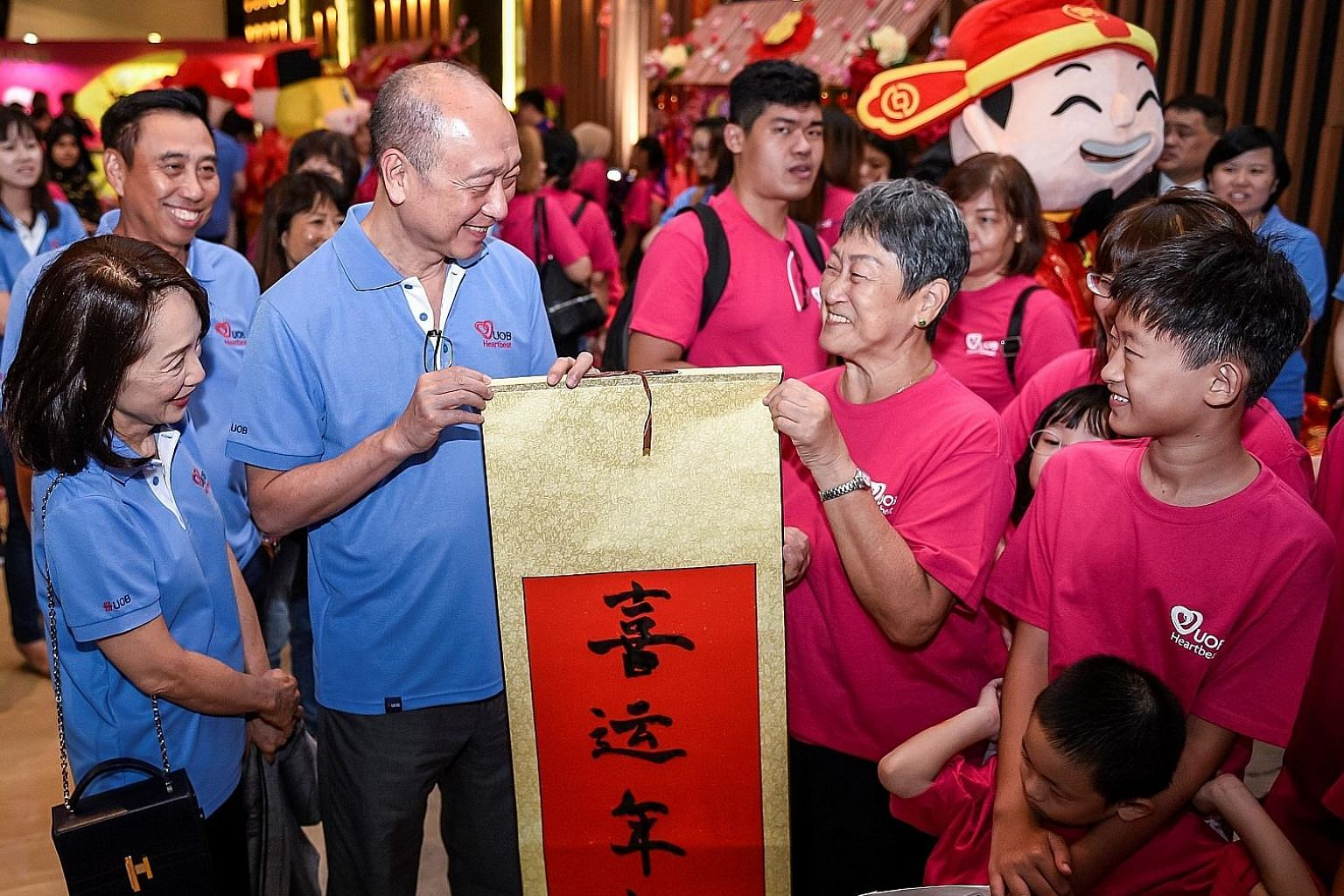 Mr Wee Ee Cheong (second from left), deputy chairman and chief executive of UOB, and Mrs Wee, seen here with Mr Eric Tham (back row, far left), head of UOB's group commercial banking, presenting a Chinese calligraphy scroll for Chinese New Year to a
