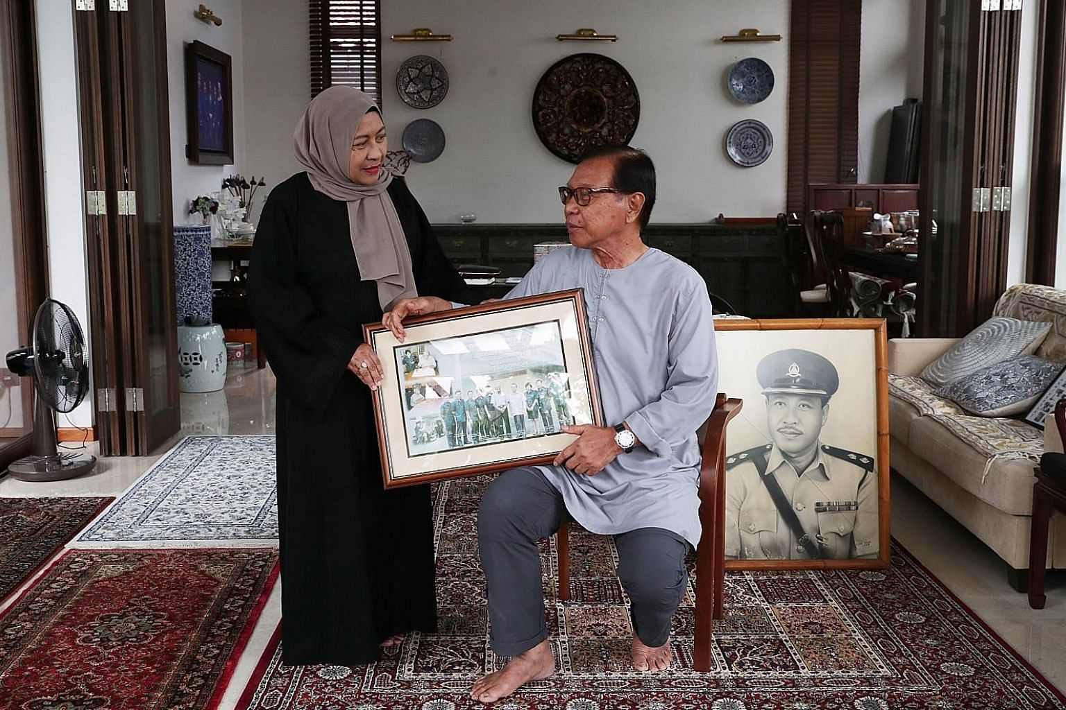 Acting Superintendent Sarpon wore sunglasses on his retirement day at Changi Prison in 1970 so no one could see his tears. Madam Norhaya Sarpon, 62, and Mr Sobahri Sarpon, 73, reminiscing with photos and stories of their late father, Mr Sarpon Muradi