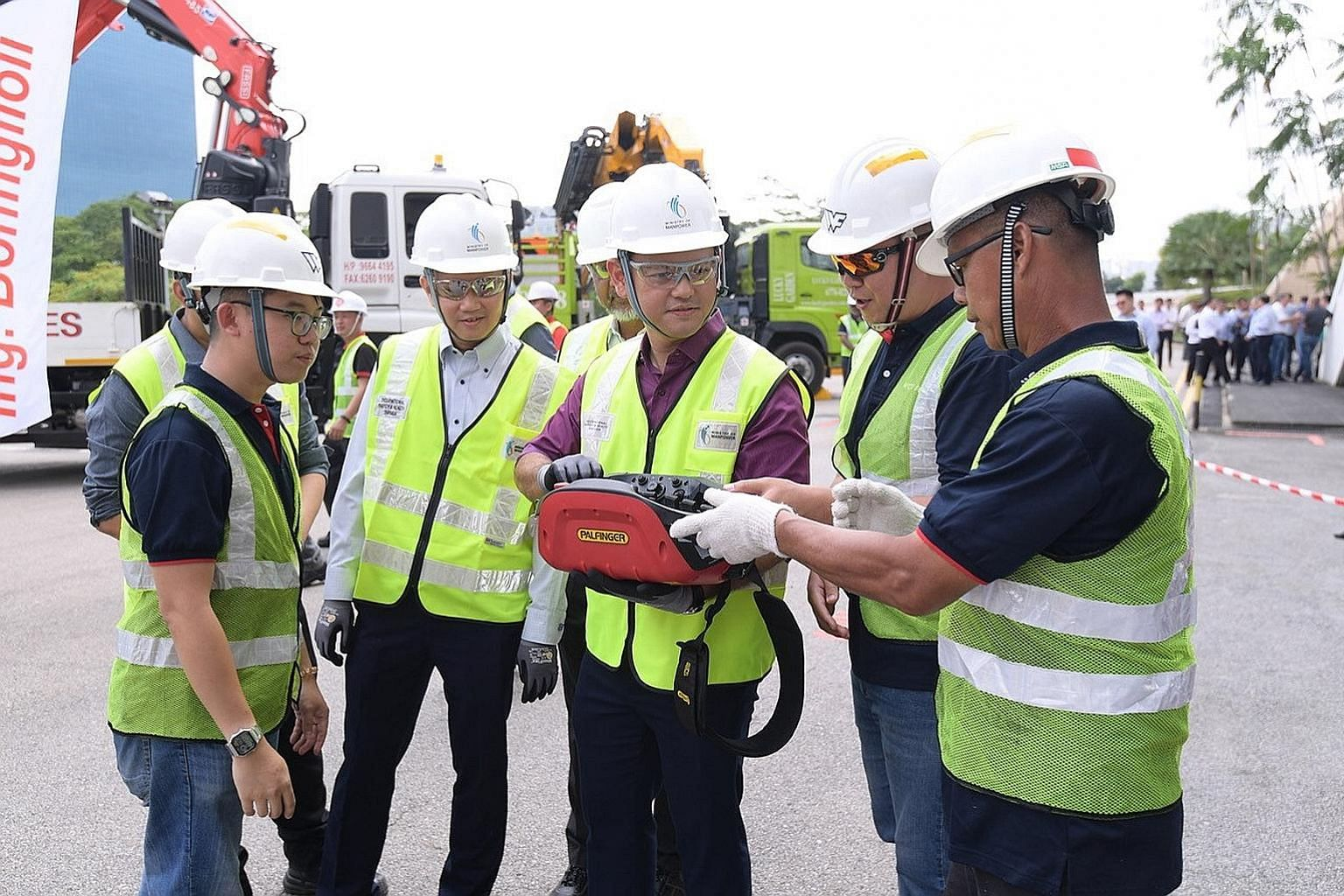 Minister of State for Manpower Zaqy Mohamad trying his hand at operating a lorry crane remotely via a control box. The Ministry of Manpower and the Workplace Safety and Health Council will launch two new sets of guidelines on the safe use of lorry cr