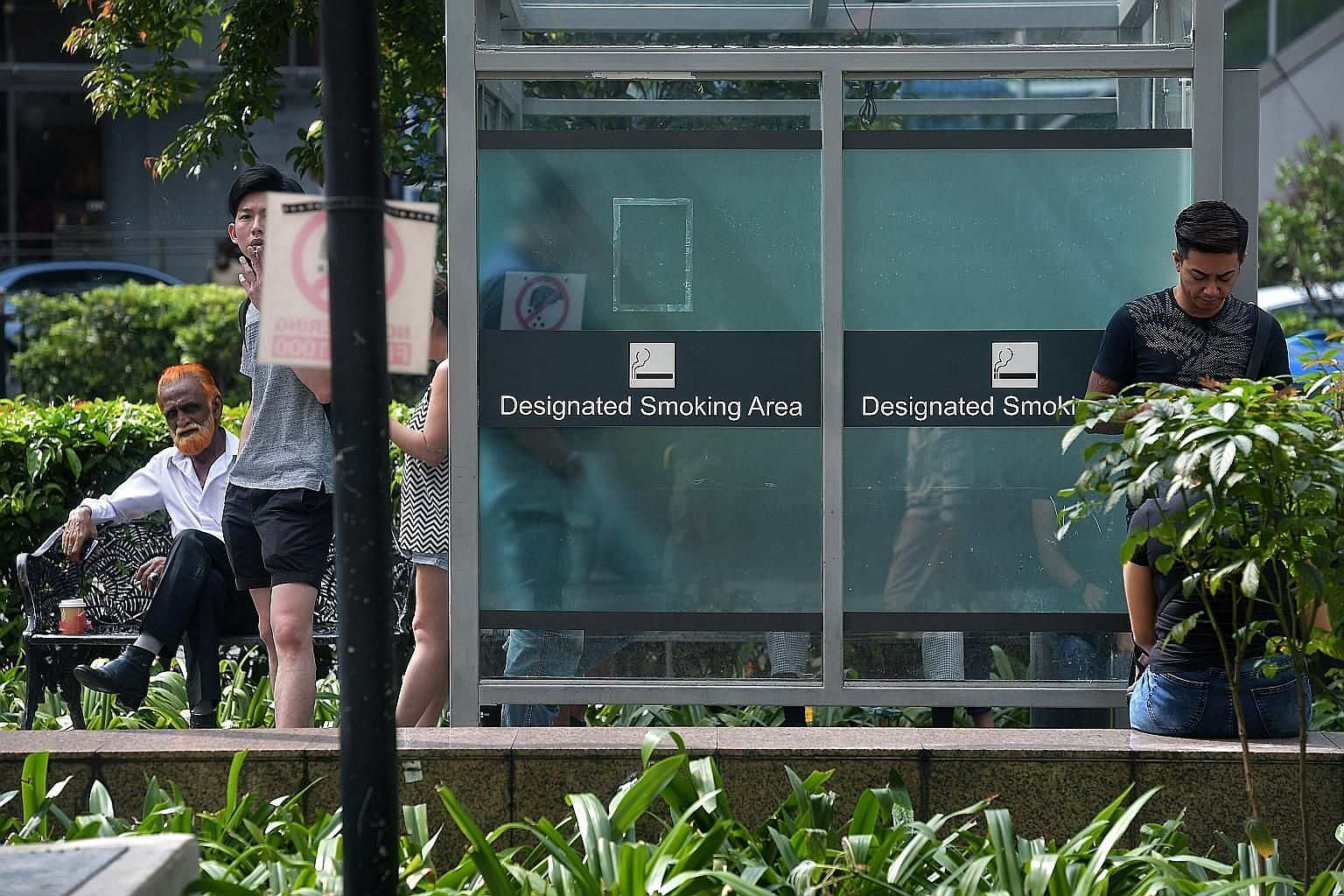 Smokers at a designated smoking area in front of Far East Plaza along Scotts Road yesterday. The National Environment Agency said that an average of 21 tickets per day were issued in the month of April last year - after enforcement began - and the nu