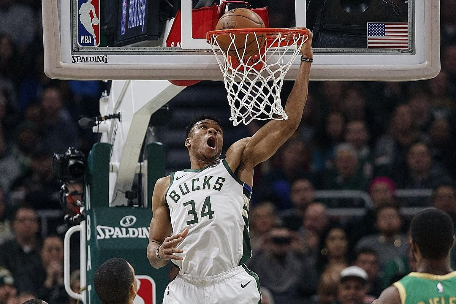 NBA MVP Giannis Antetokounmpo downing two of his 32 points in the Milwaukee Bucks' 128-123 win over the Boston Celtics on Thursday, which extended the Eastern Conference leaders' winning streak to five games.