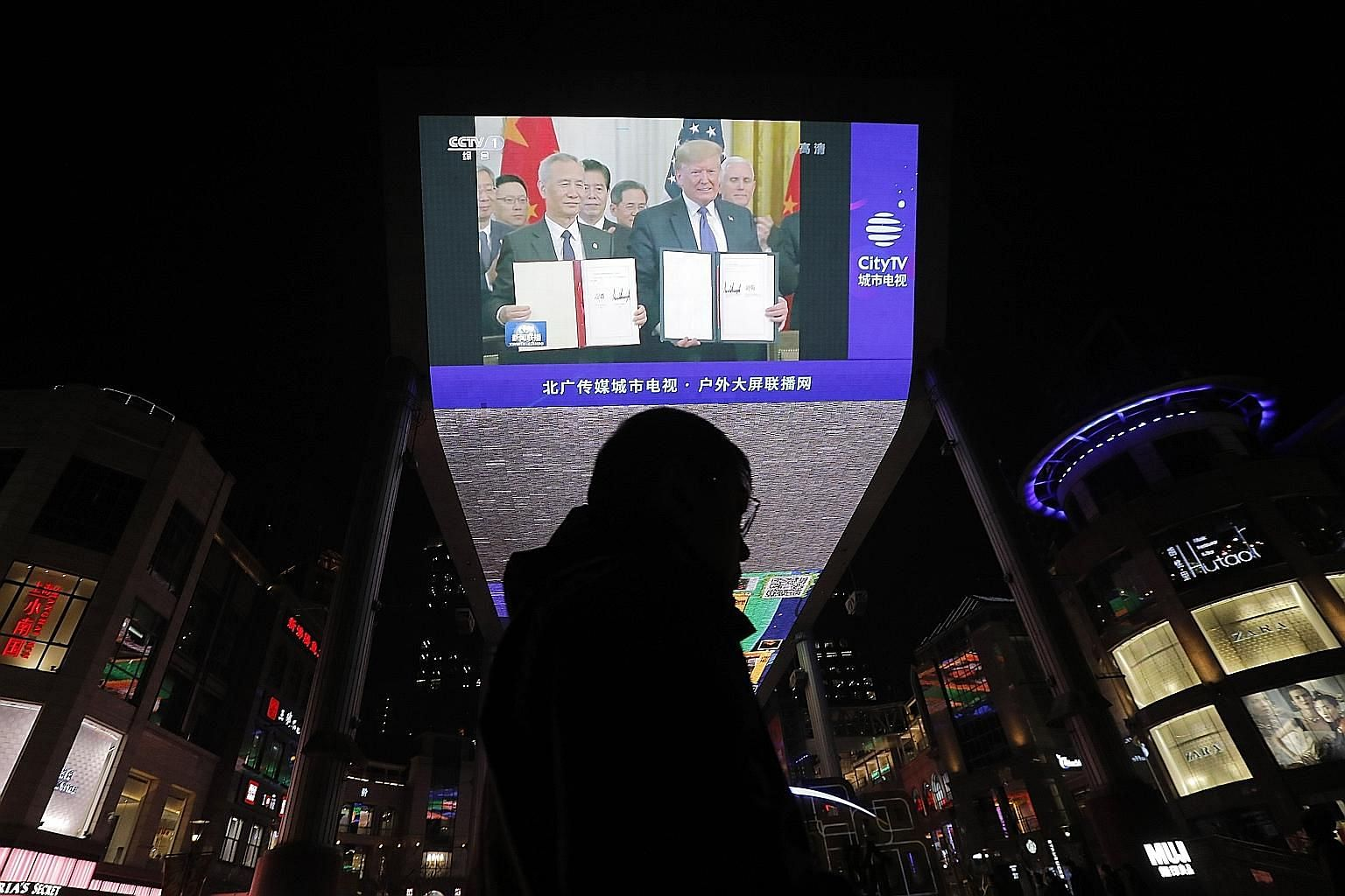 A TV screen outside a shopping mall in Beijing showing US President Donald Trump and Chinese Vice-Premier Liu He during the signing of the phase one trade agreement last Thursday. Mr Trump and Chinese Vice-Premier Han Zheng are expected to deliver sp