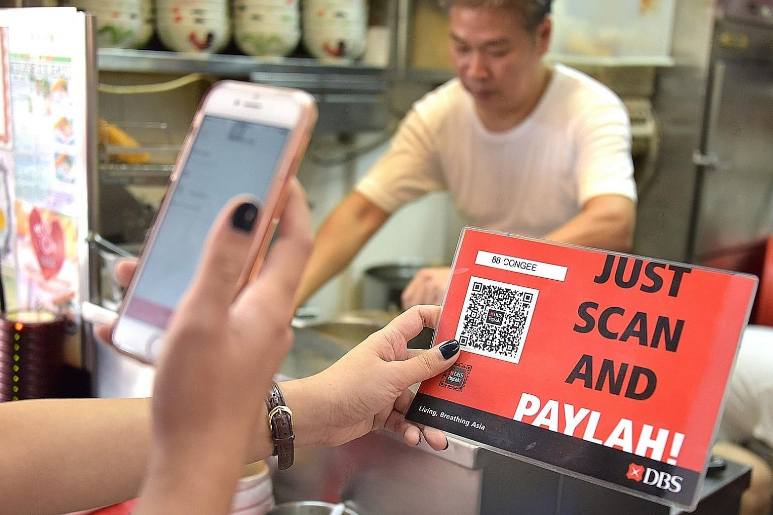A customer paying for food using mobile payment app DBS PayLah at a hawker centre. This app, says DBS chief executive Piyush Gupta, is an example of how the bank leverages ecosystems to be where clients are.
